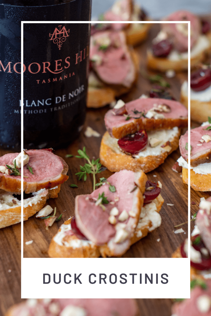 duck crostinis with cherries & goat cheese on wooden chopping board & moores hill blanc de noir