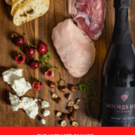 duck breast, goat cheese, baguette & bottle of moores hill sparkling wine on a chopping board