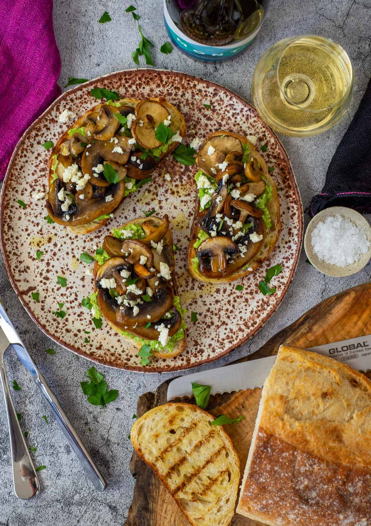 mushroom avocado toast on a plate with bread on chopping board and mont wines chardonnay