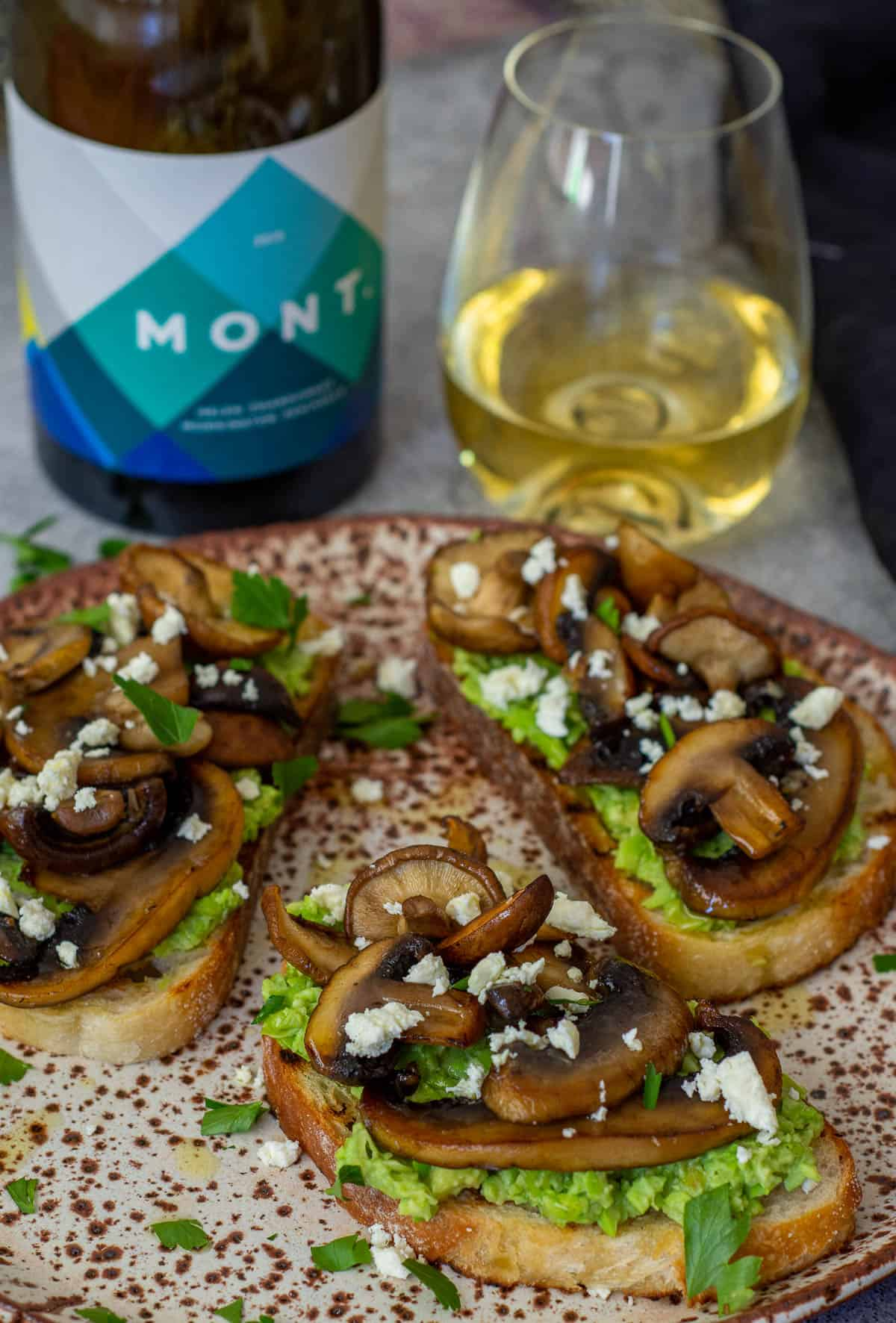 mushroom avocado toast on a plate with Mont chardonnay in background