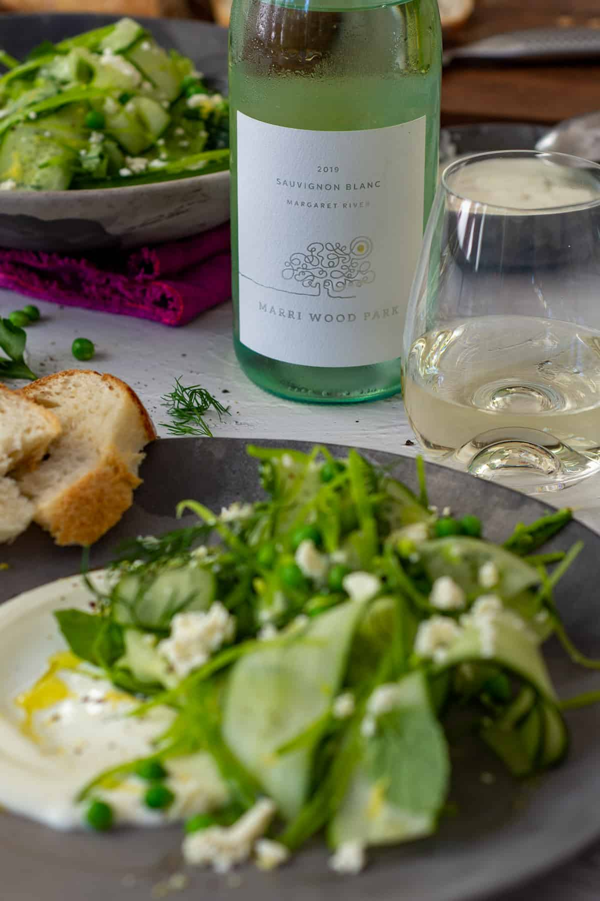 English pea salad on a plate, sourdough bread & Marri wood park sauvignon blanc