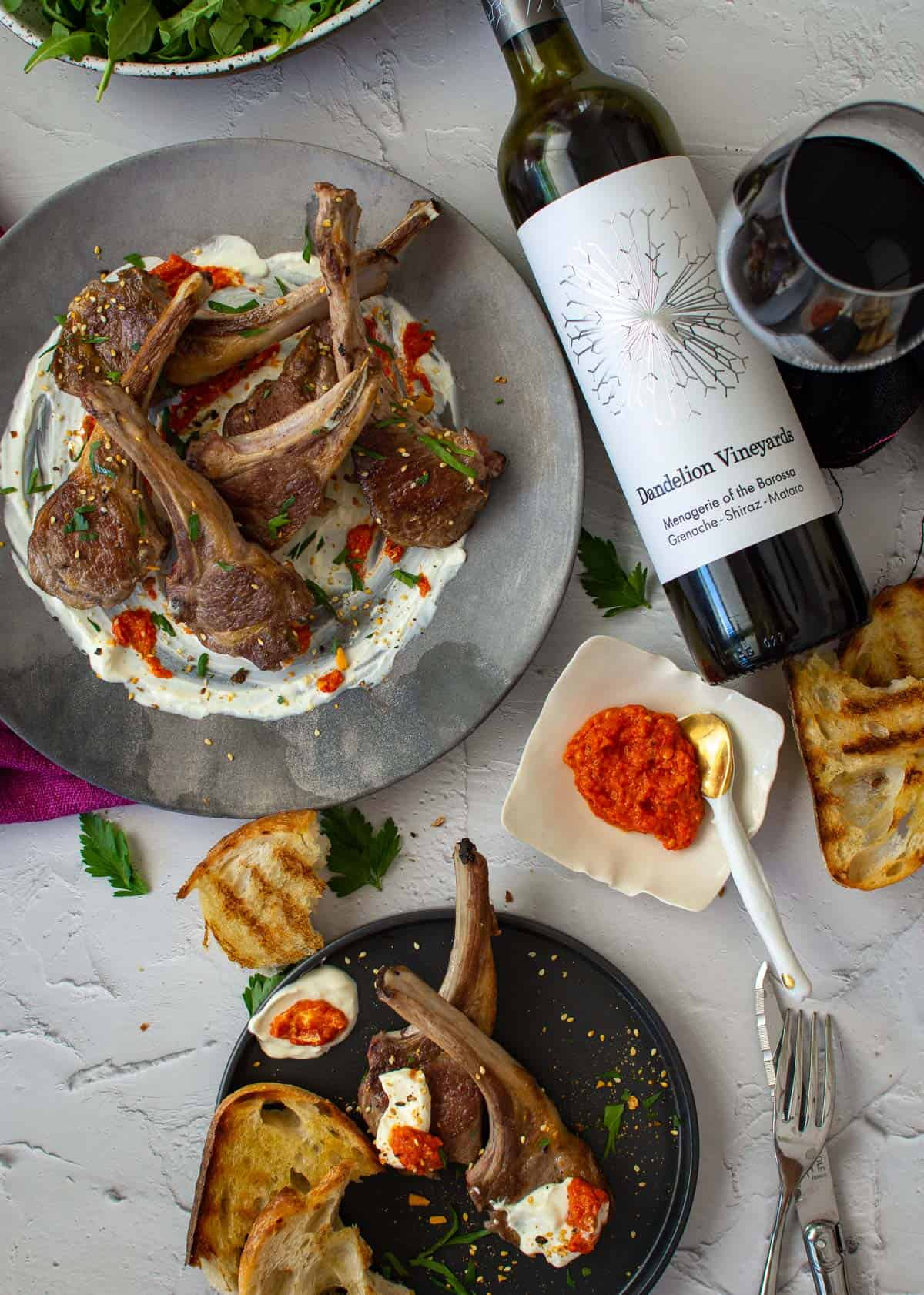 dandelion gsm wine, grilled bread and grilled lamb chops on a plate with harissa and labneh