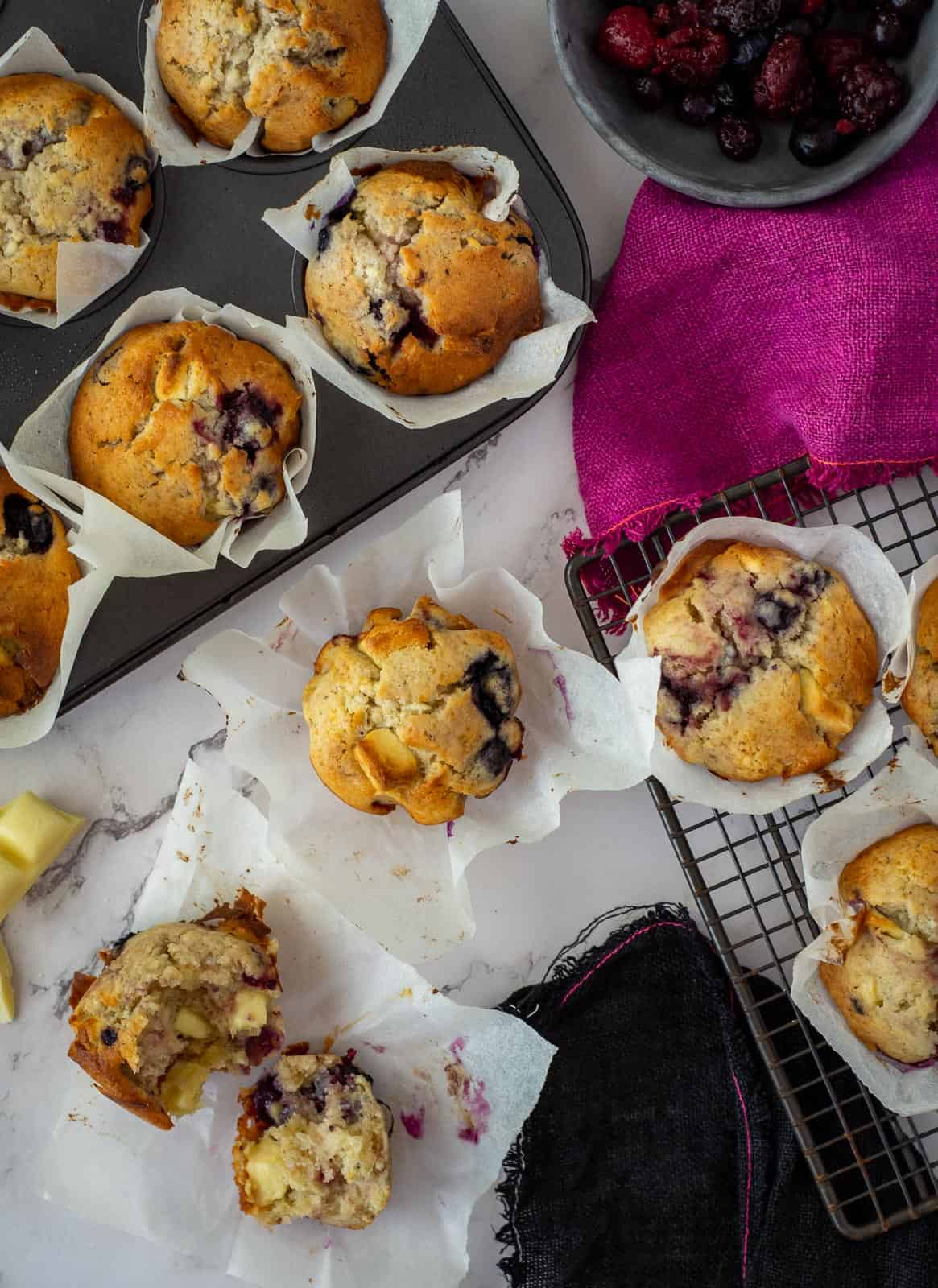 white chocolate muffins on countertop, some on a wire rack and in a muffin tray