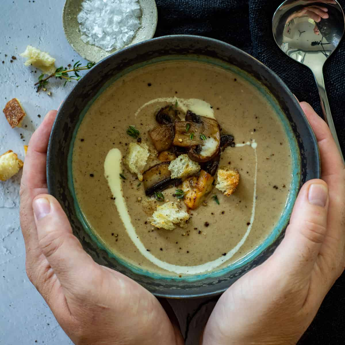 someone cupping a bowl of dried porcini mushroom parsnip soup