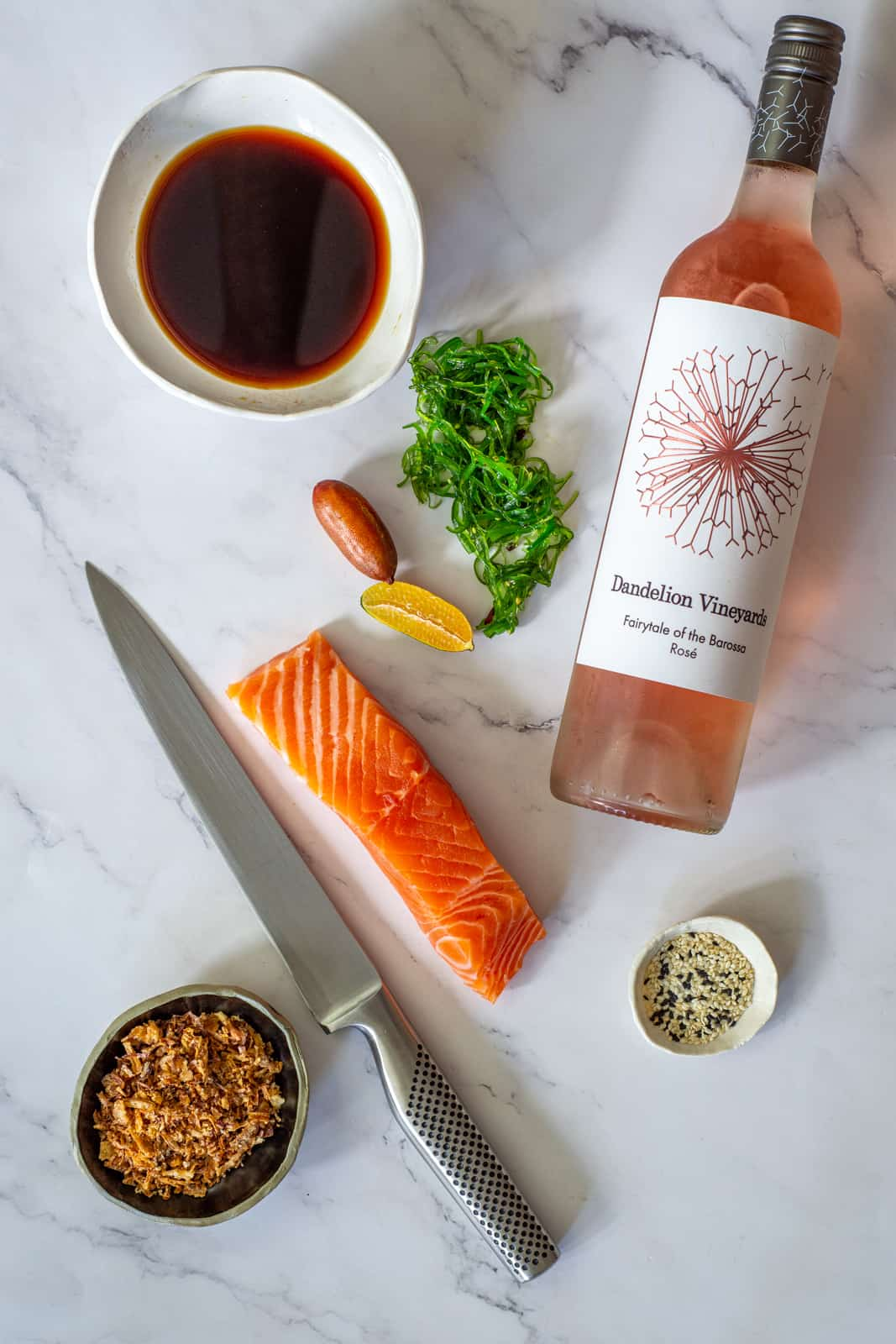 Dandelion rose, ponzu sauce, raw salmon & a global knife on a counter top