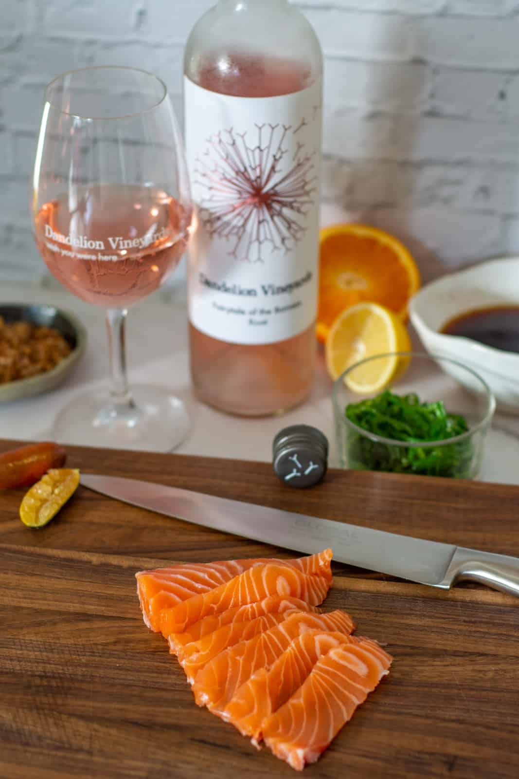 sliced raw salmon on a chopping board, dandelion rose & ponzu sauce ingredients in background