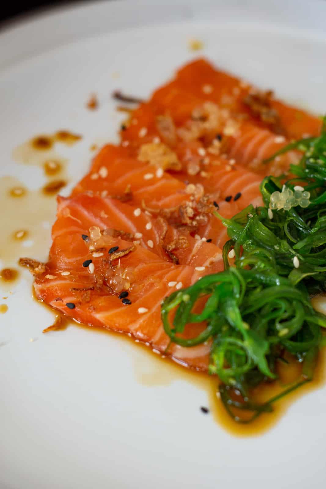 close up of salmon crudo w/ ponzu sauce & wakame on a white plate