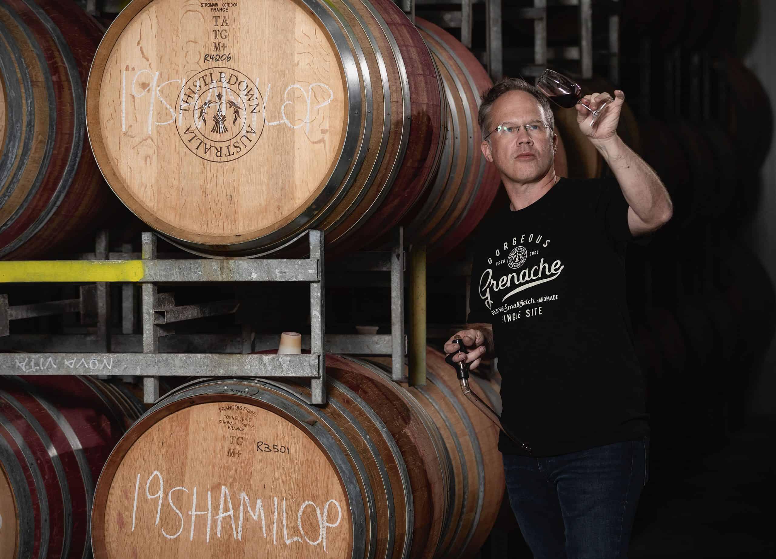 Giles inspecting wine beside wine barrels