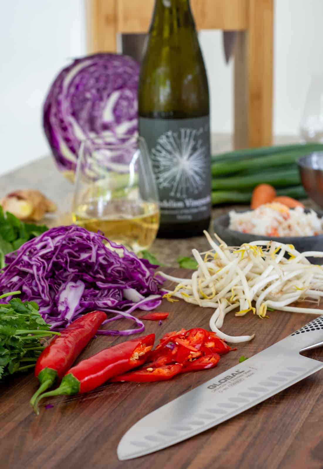 vegetables on a global chopping board with global chef knife on kitchen counter top