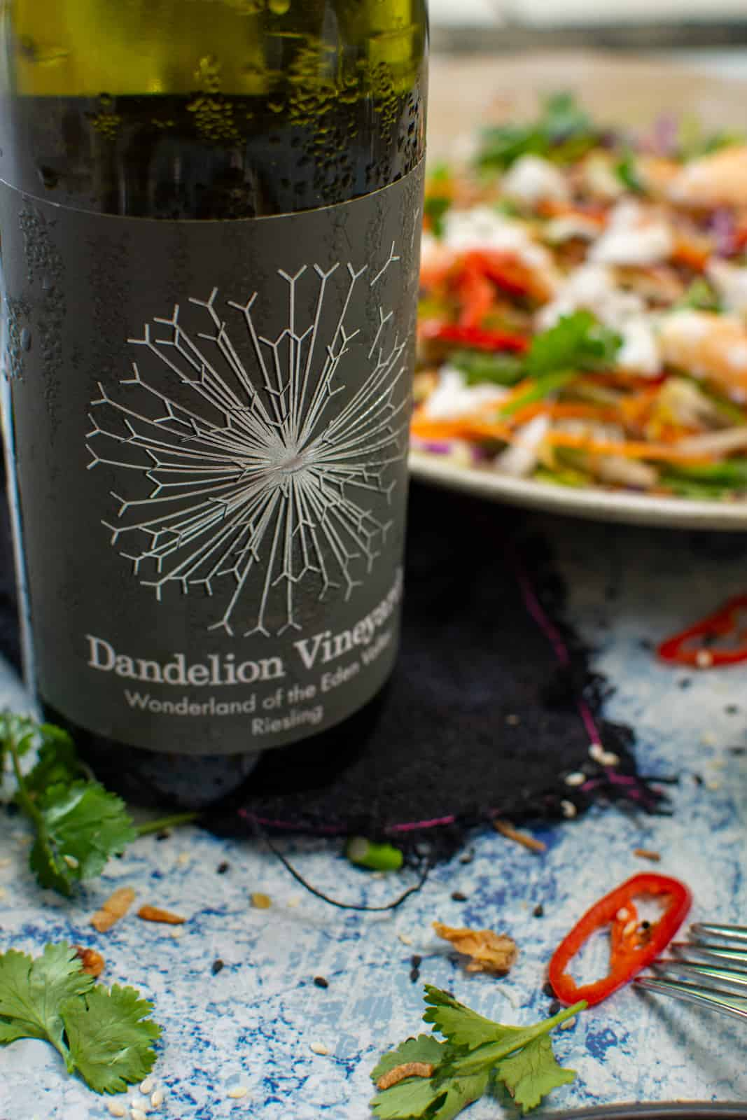 close up of dandelion riesling with spicy crab salad in background