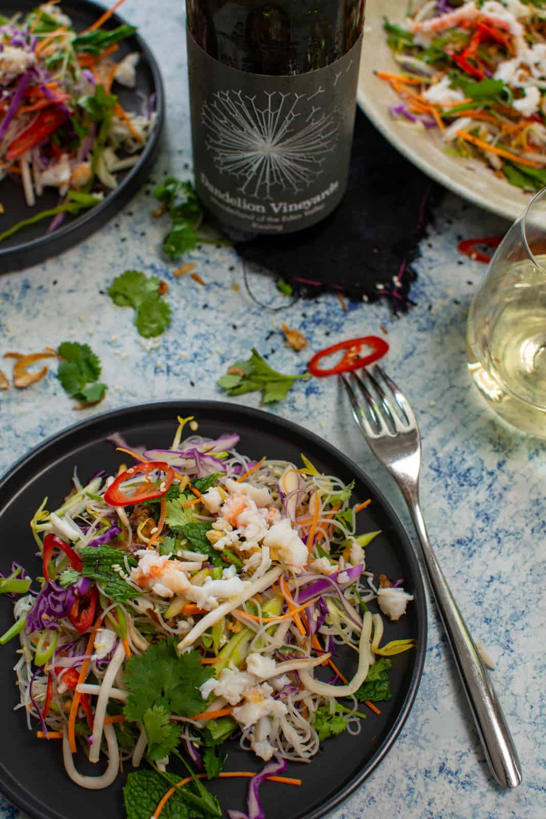 spicy crab salad on a black plate with a fork and a bottle of dandelion riesling on table