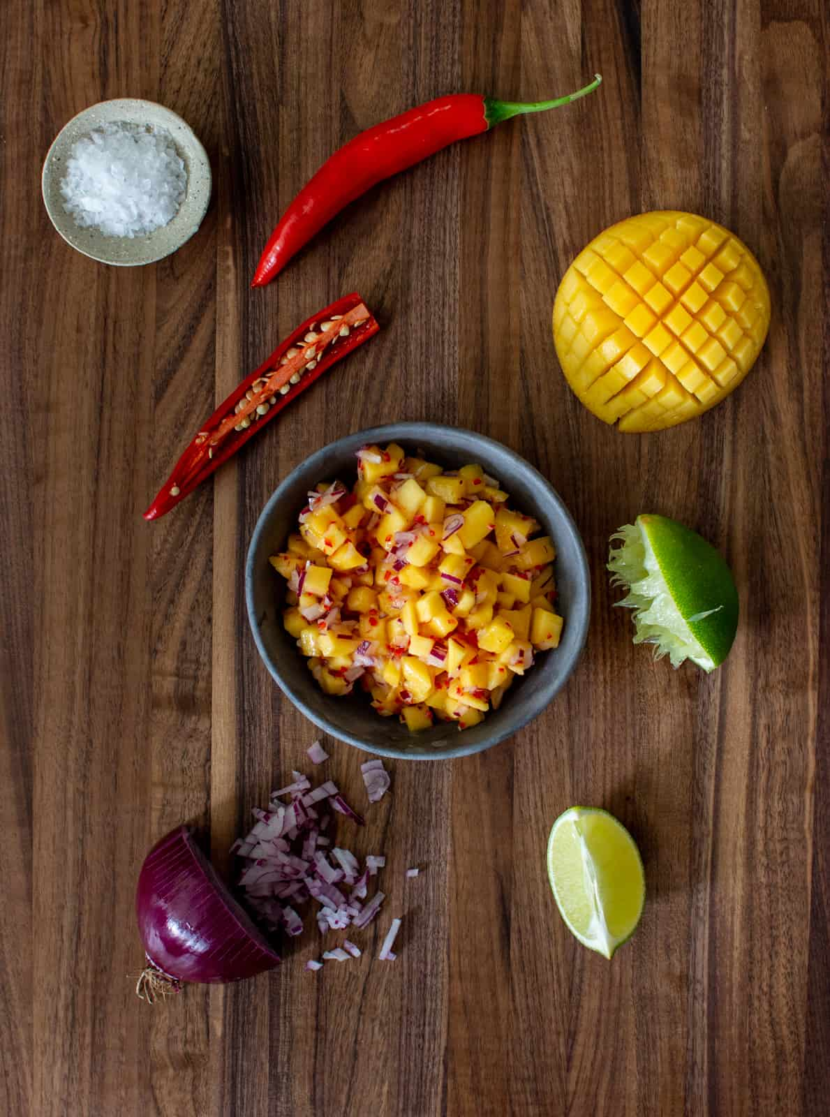 spicy mango salsa in a bowl on a wooden chopping board with salsa ingredients beside it
