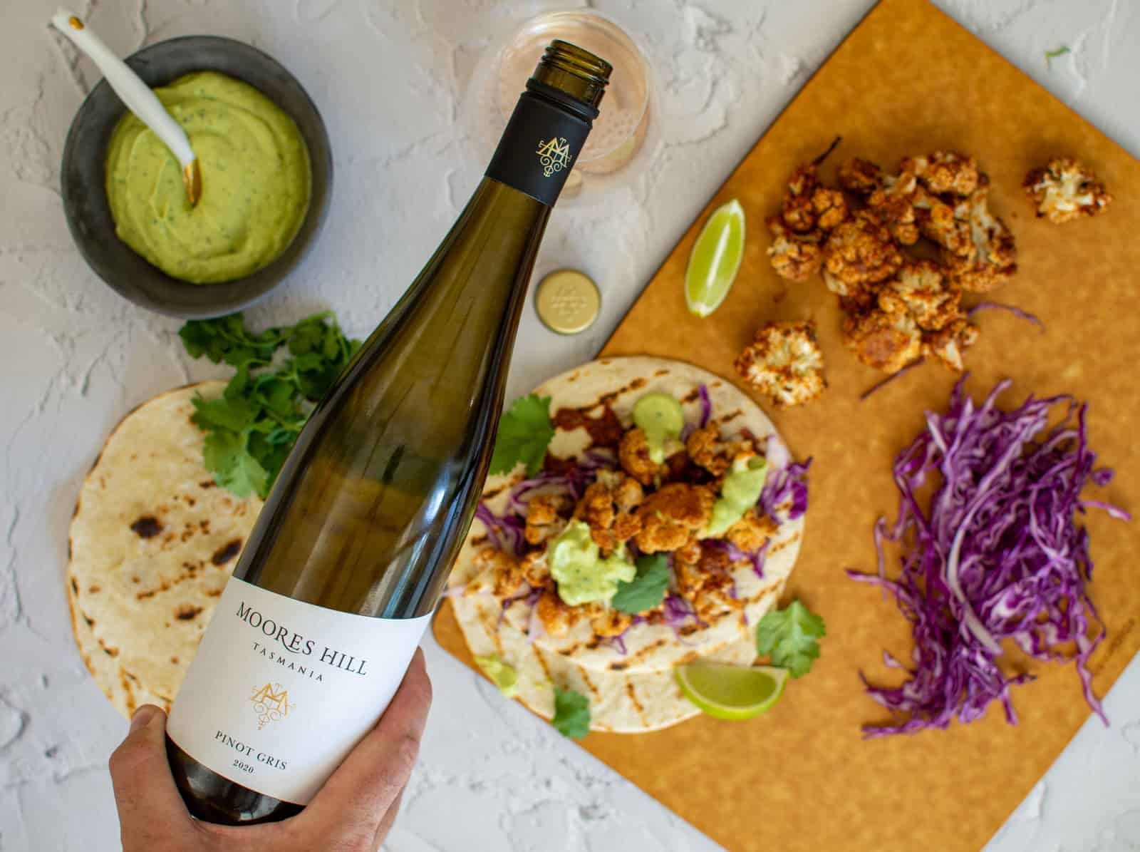 moores hill pinot gris being poured from above - cauliflower tacos beneath the bottle