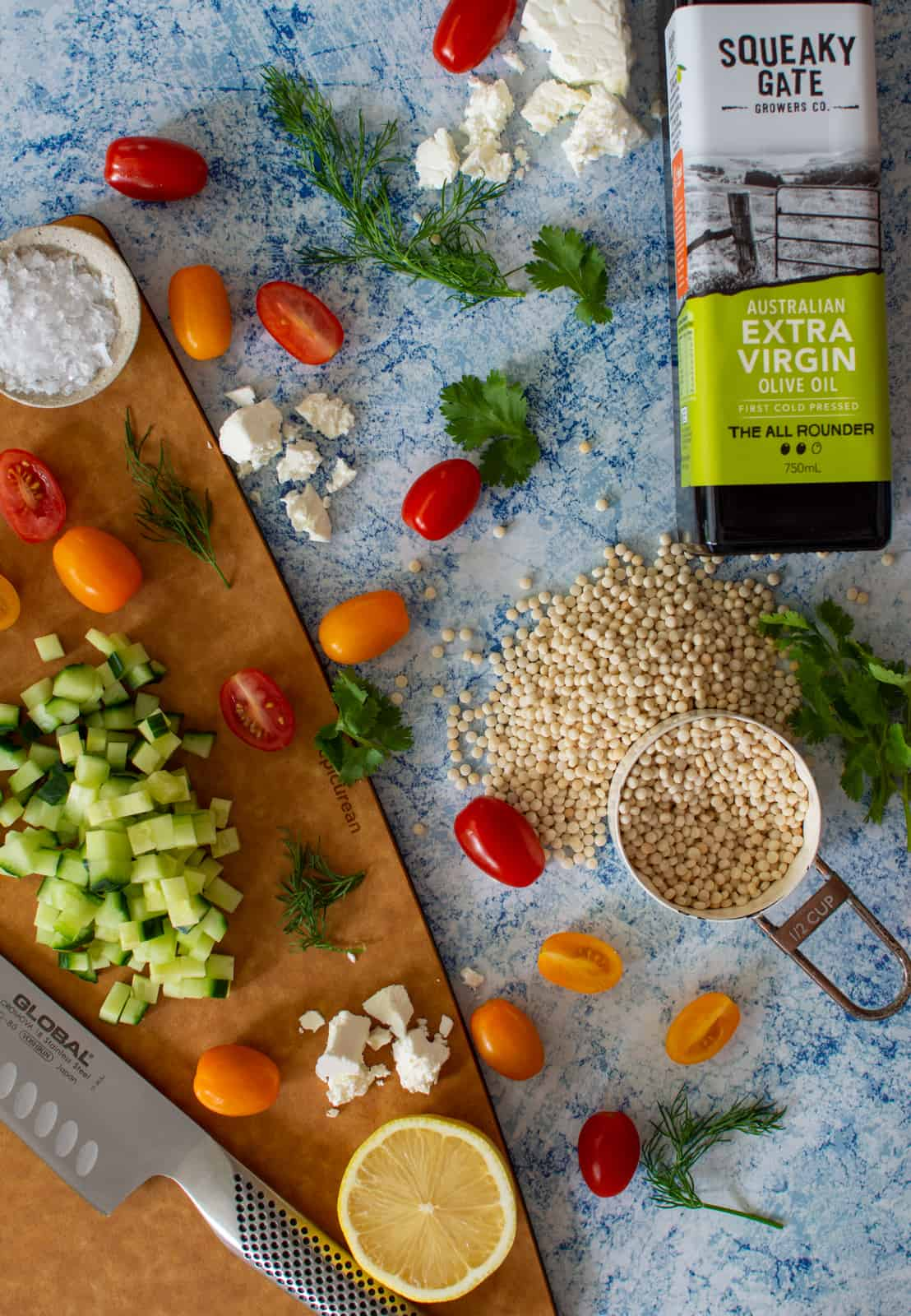 squeak gate olive oil, pearl cous cous and vegetables on a chopping board