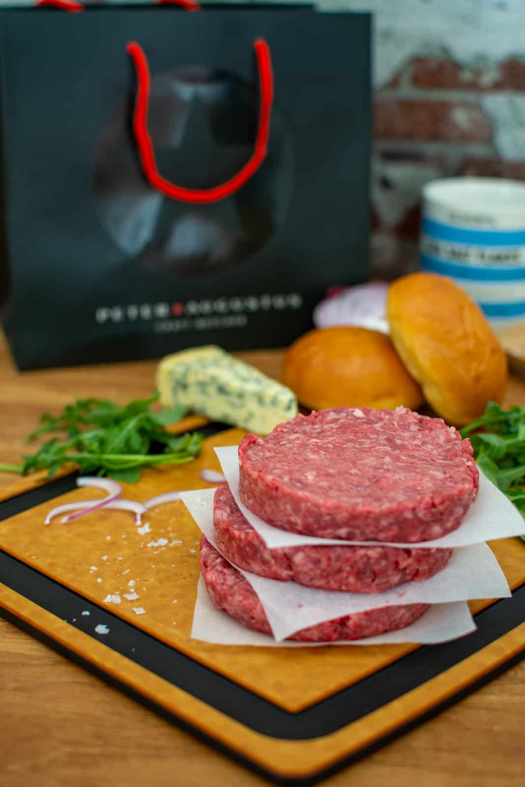 wagyu burger patties on a chopping board with rocket, onion, blue cheese & burger buns