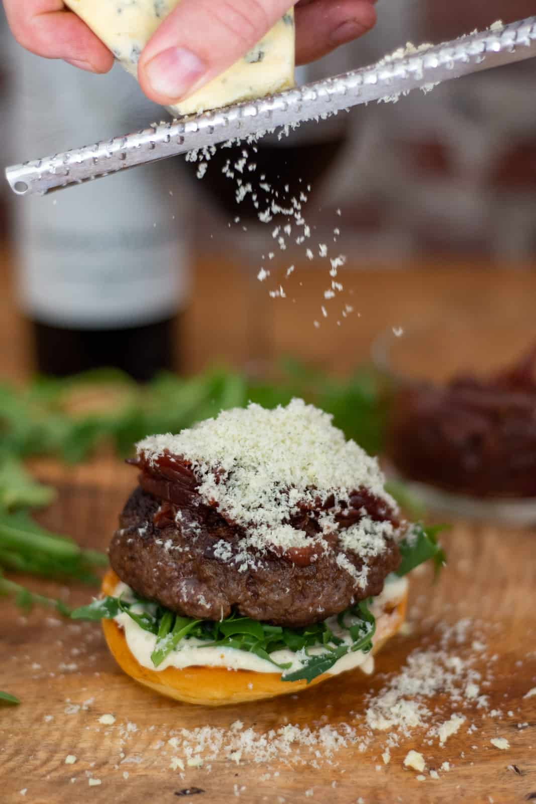 wagyu beef burger on board with frozen blue cheese being grated on top