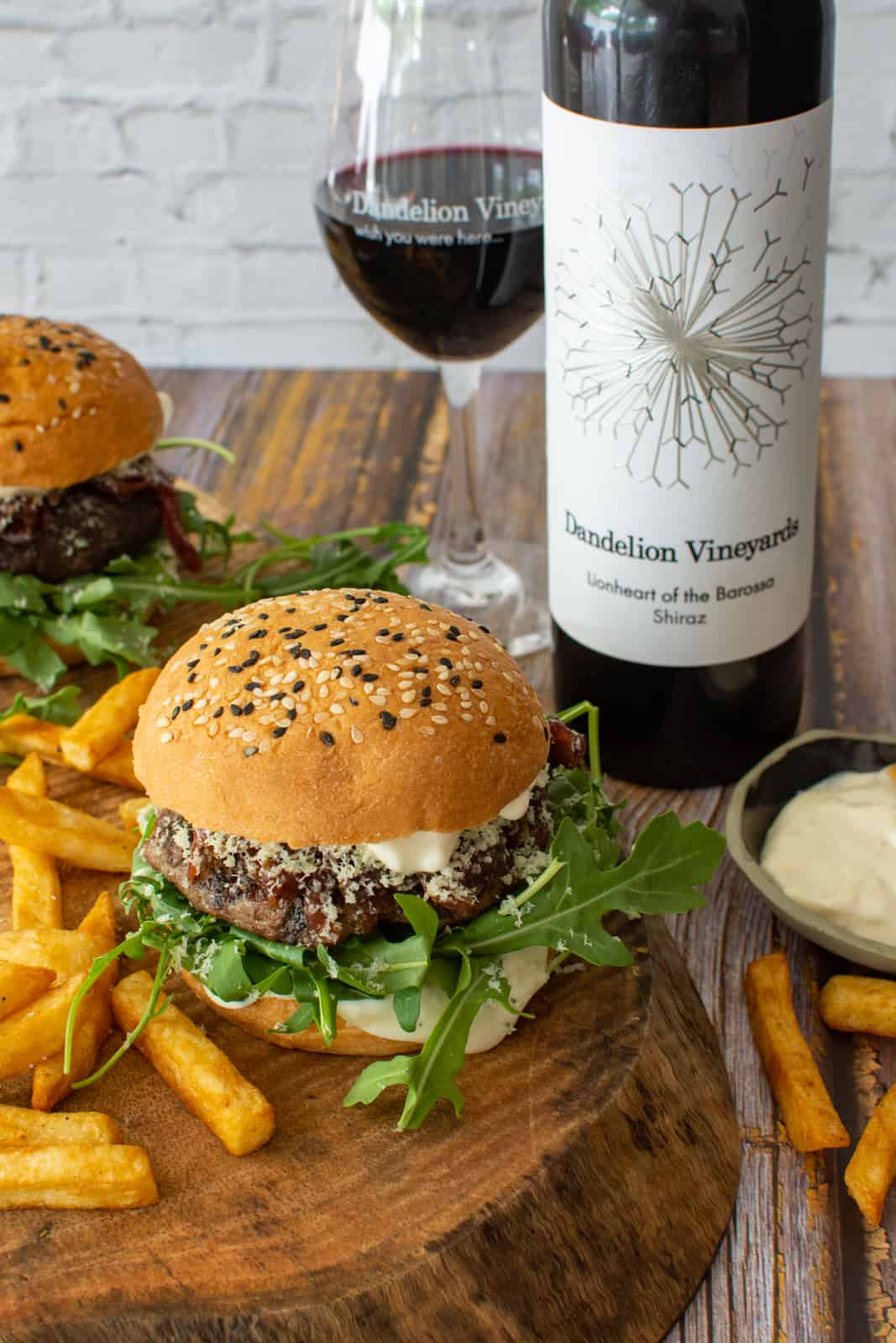 Two wagyu beef burgers on wooden board with chips and bottle of Dandelion lionheart shiraz