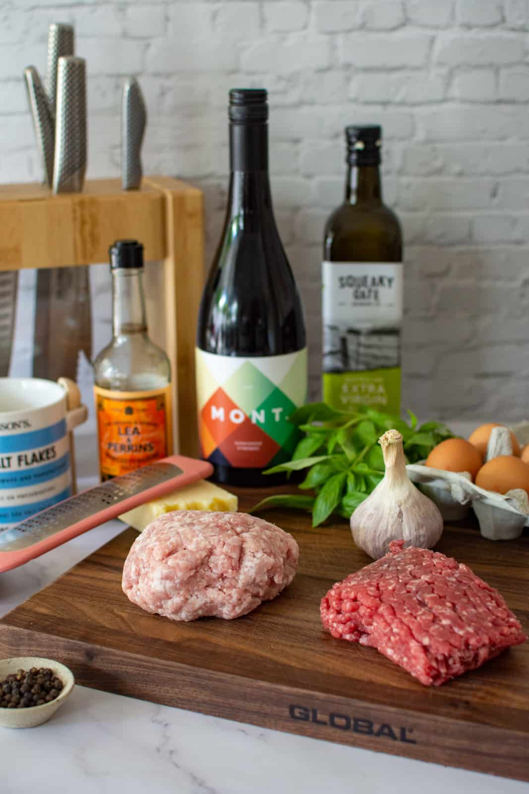 pork & beef mince on a chopping board, mont wine in background and ingredients to make meatballs marinara