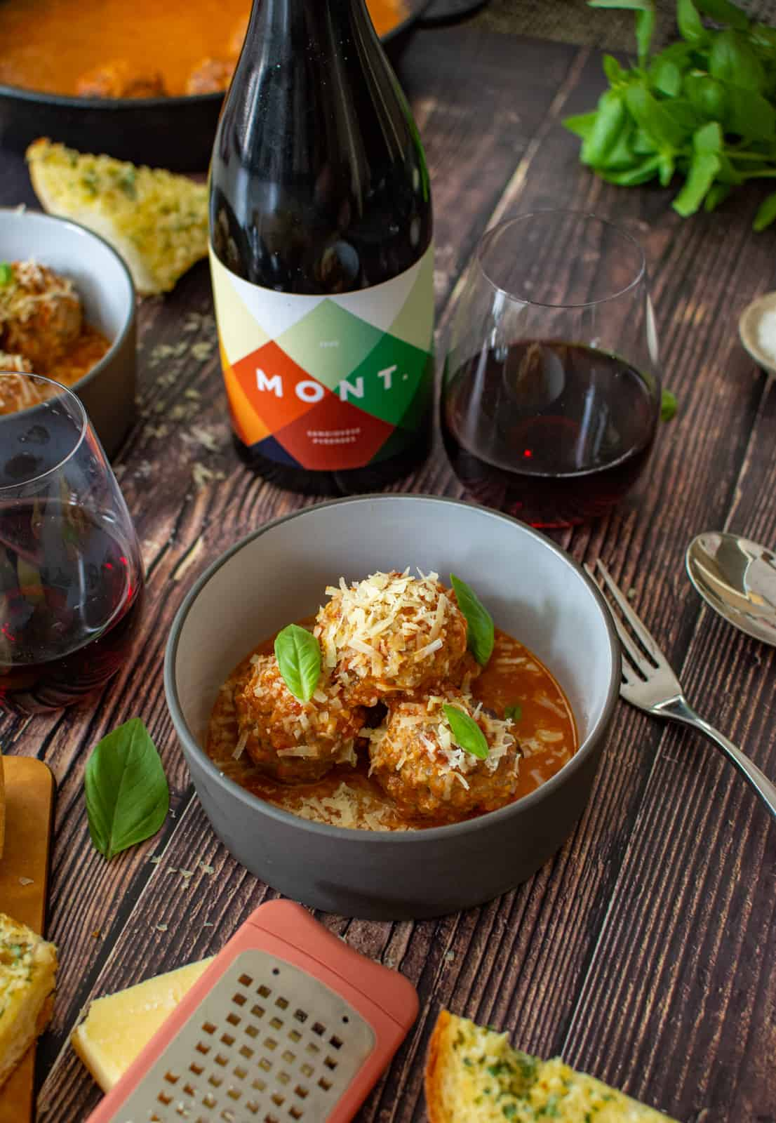 bowl of pork & beef meatballs, marinara sauce, parmsan and some wine in glasses on wooden table
