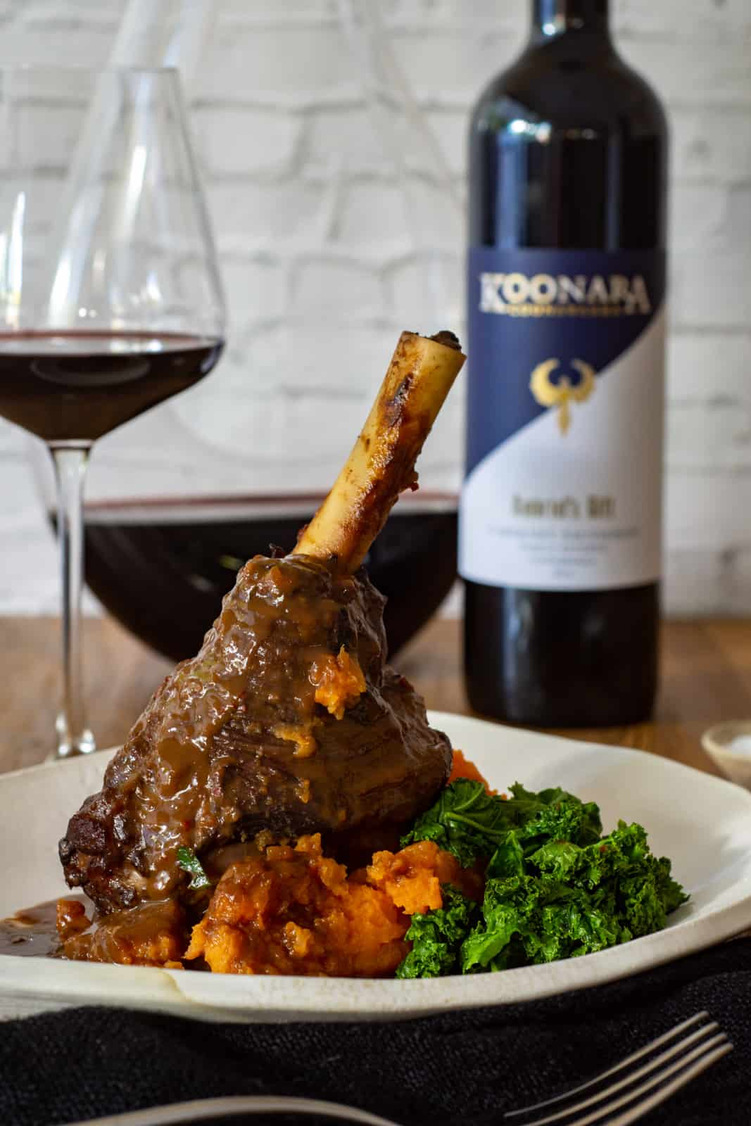 chilli & chocolate braised lamb shanks on a white plate with koonara cabernet sauvignon in background