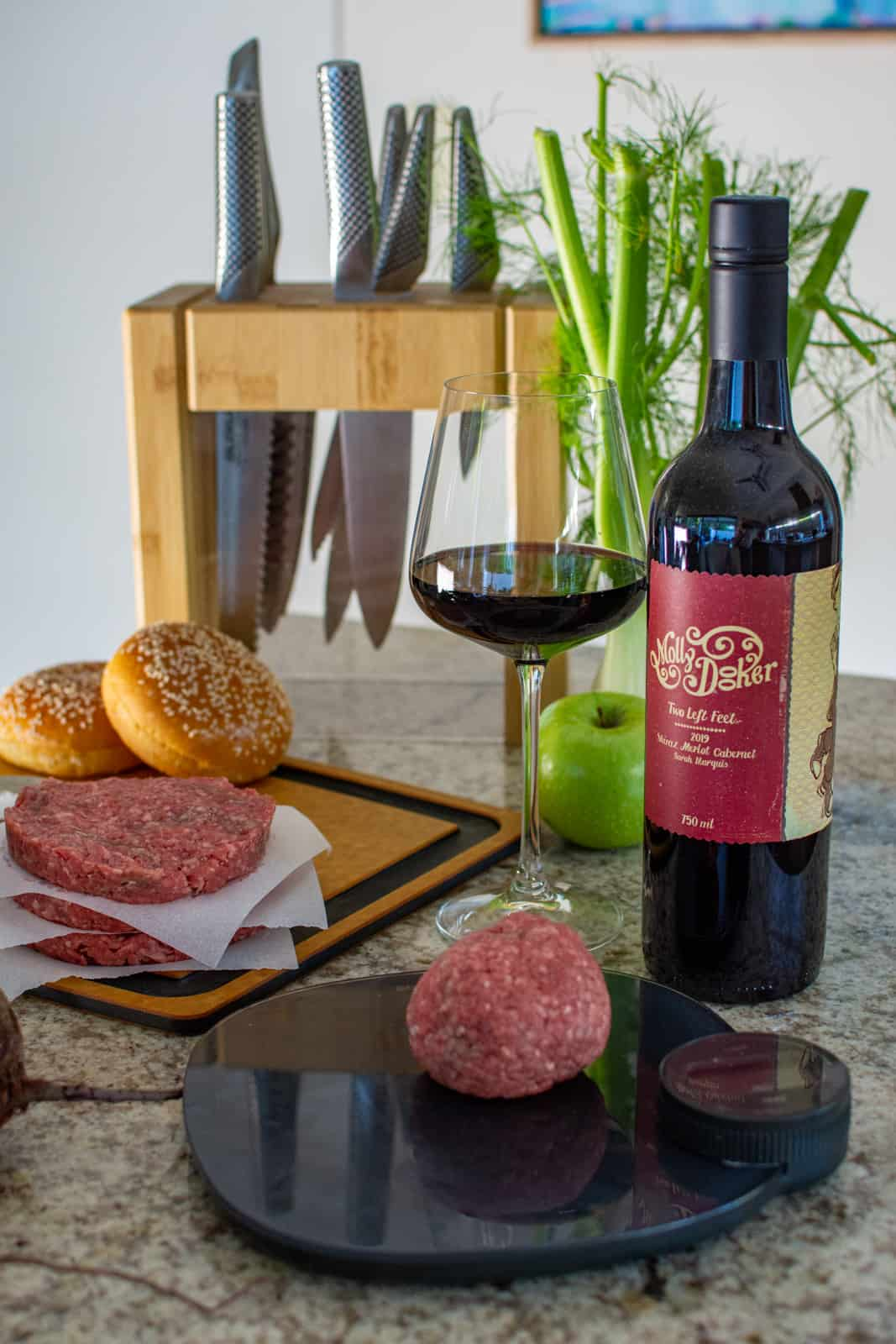 beef mince on a weighing scles with beef burger patties and a bottle of mollydooker wine behind it