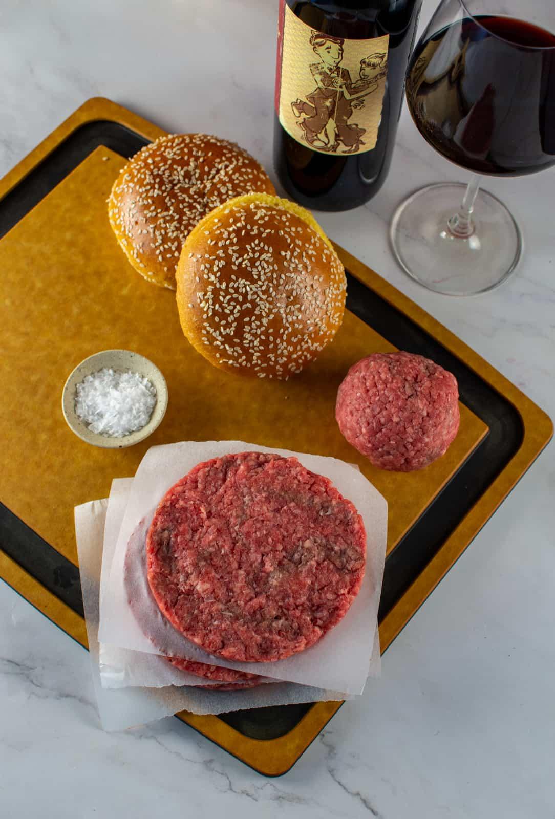 beef patties, salt, brioche buns on a chopping board with red wine beside it