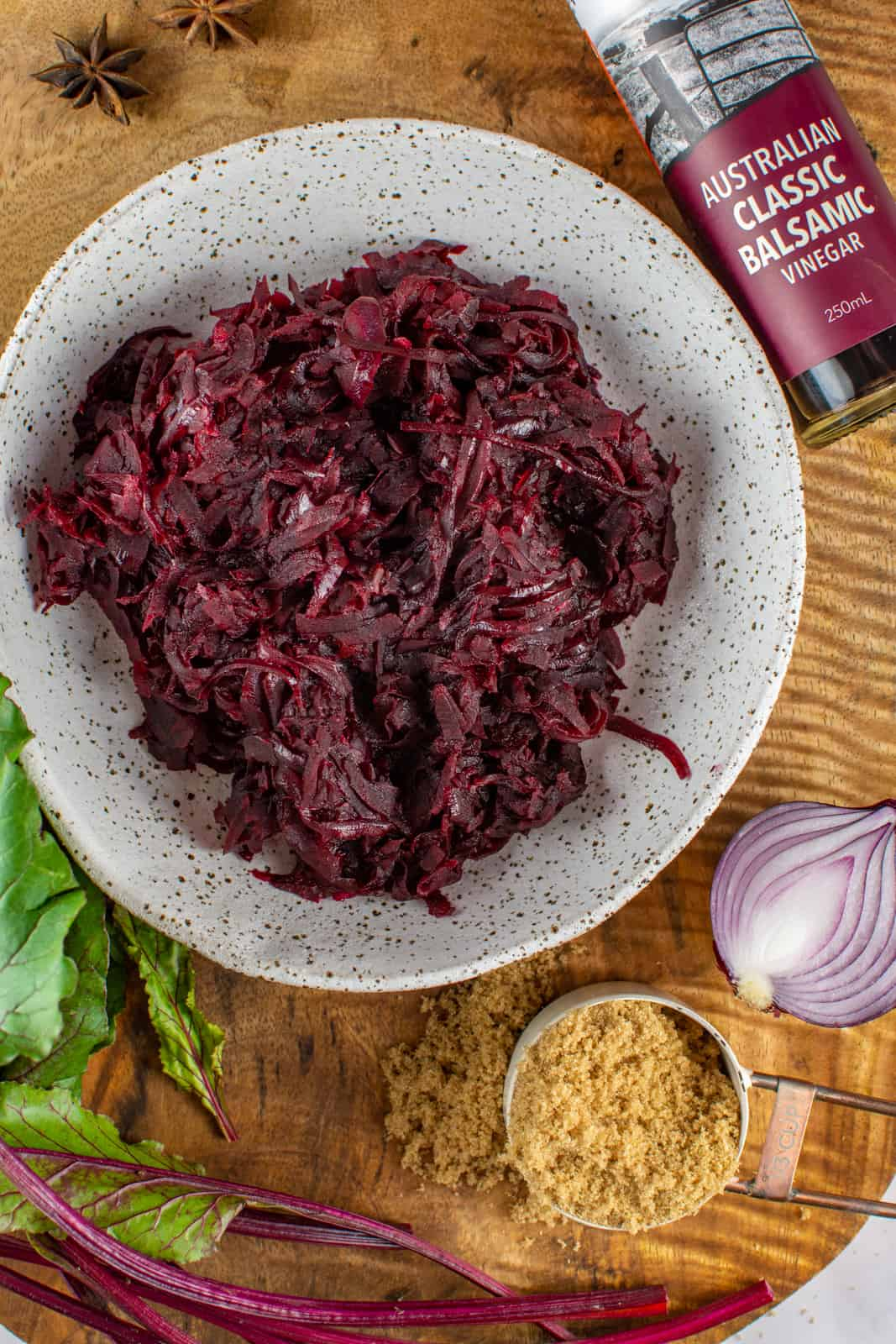 spicy beetroot relish in a white bowl on a wooden board with balsamic vinegar, beets, anise and sugar