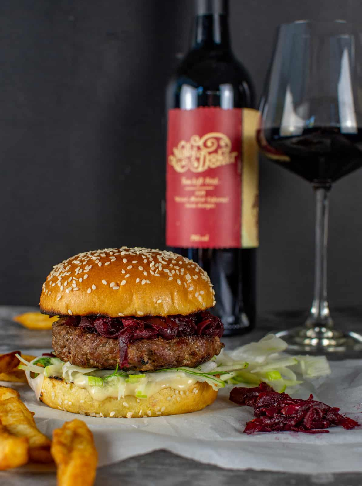 beef burger on parchmant paper with mollydooke wine behind it