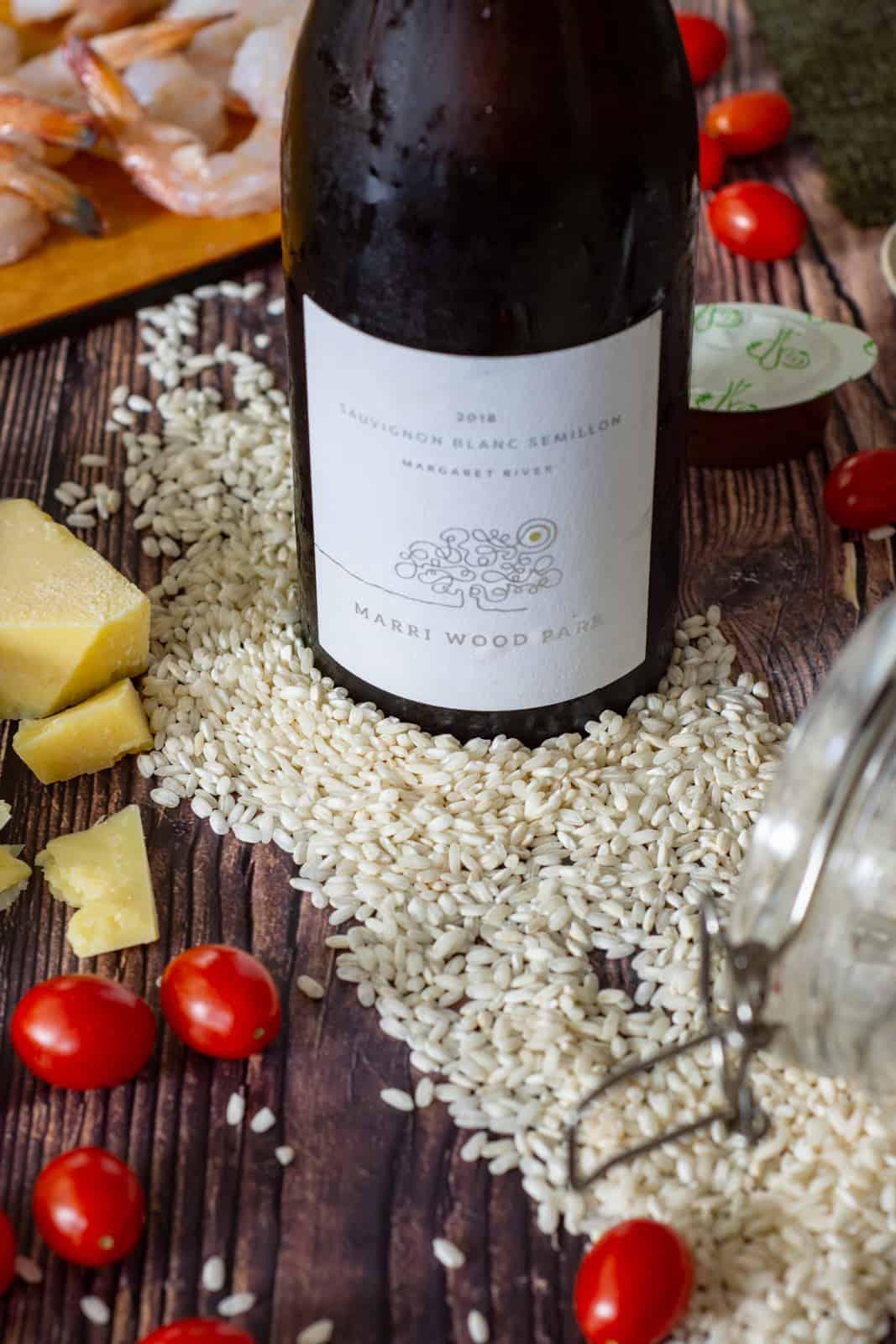 marri wood park sauvignon/semillon wine, arborio rice, tomatoes and parmesan on a wooden table