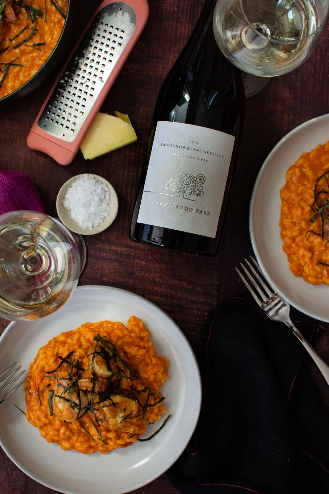prawn risotto in a white bowl, parmesan, salt and a bottle of marri wood wine on wooden table