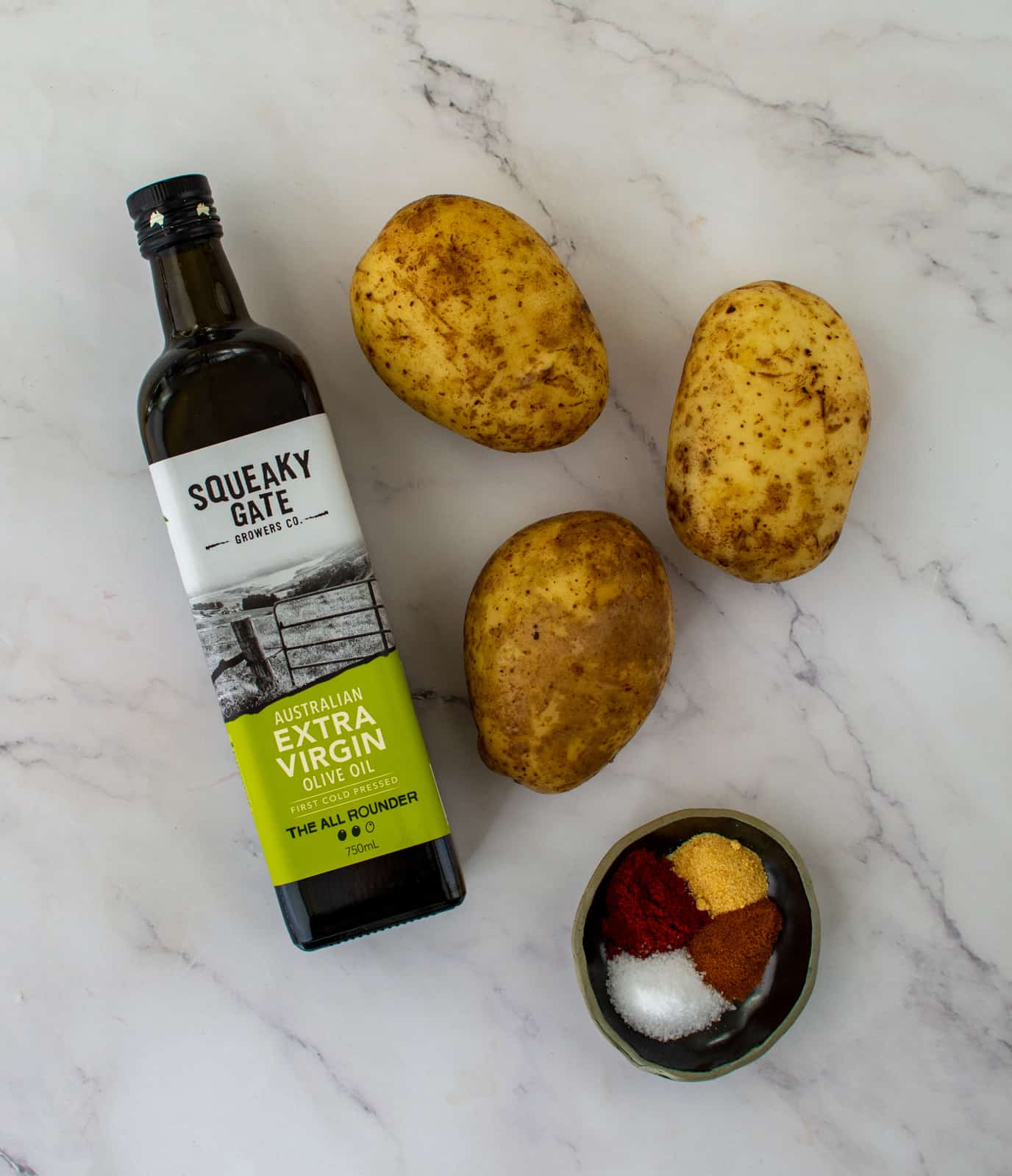 potatoes, olive oil and spices on kitchen counter