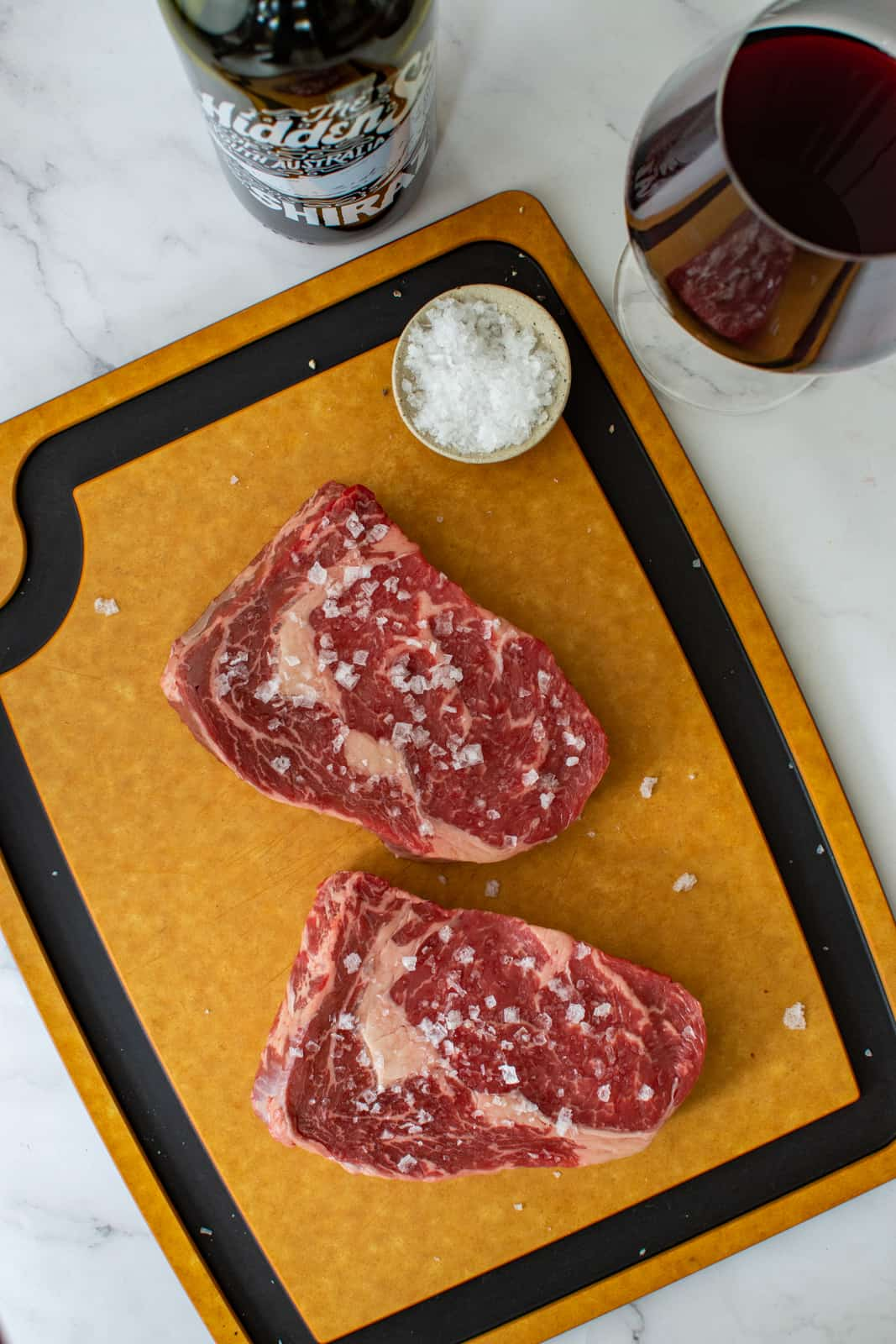 scotch fillet steaks on chopping board with hidden sea shiraz next to them