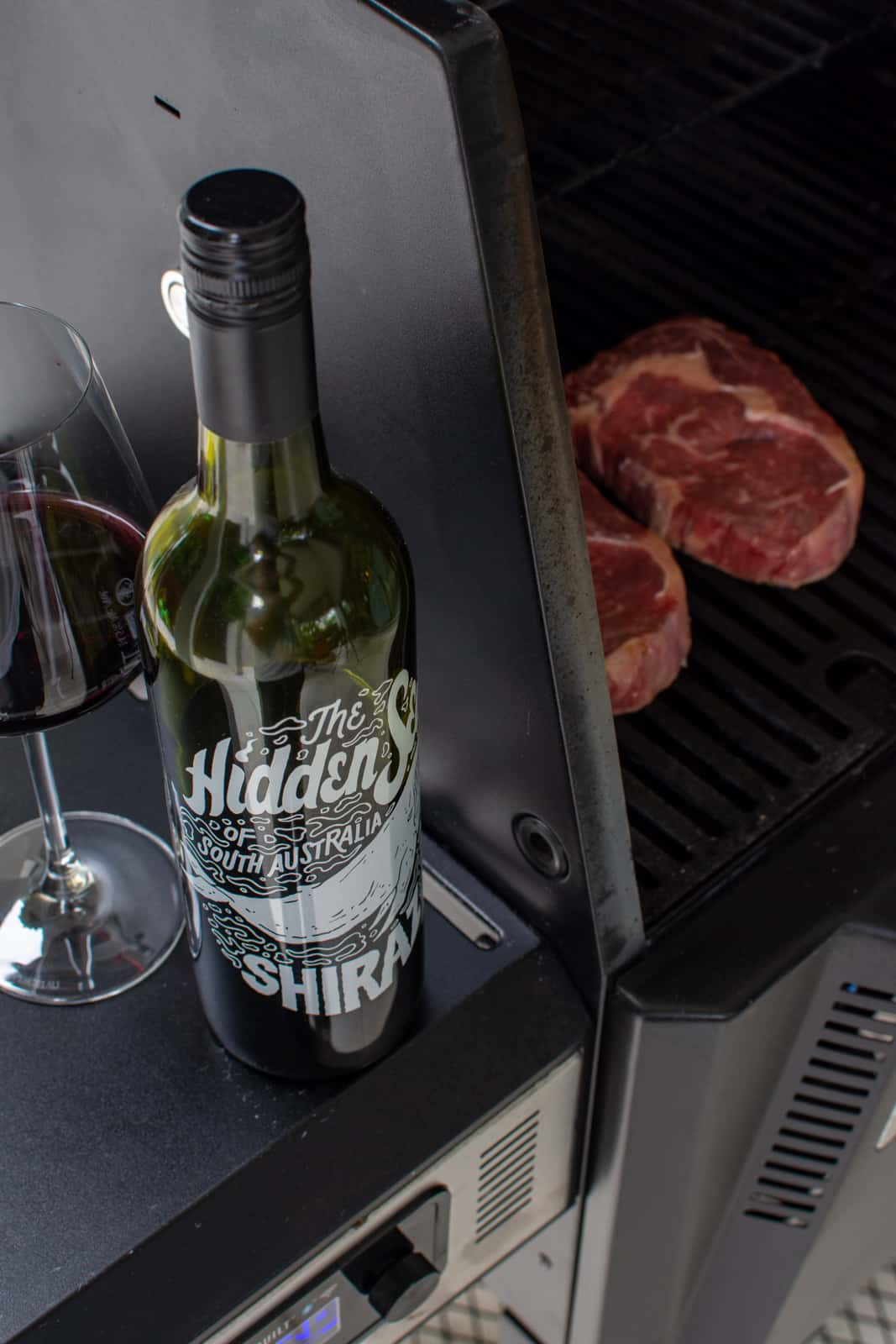 hidden sea shiraz next to BBQ with a couple scotch steaks cooking