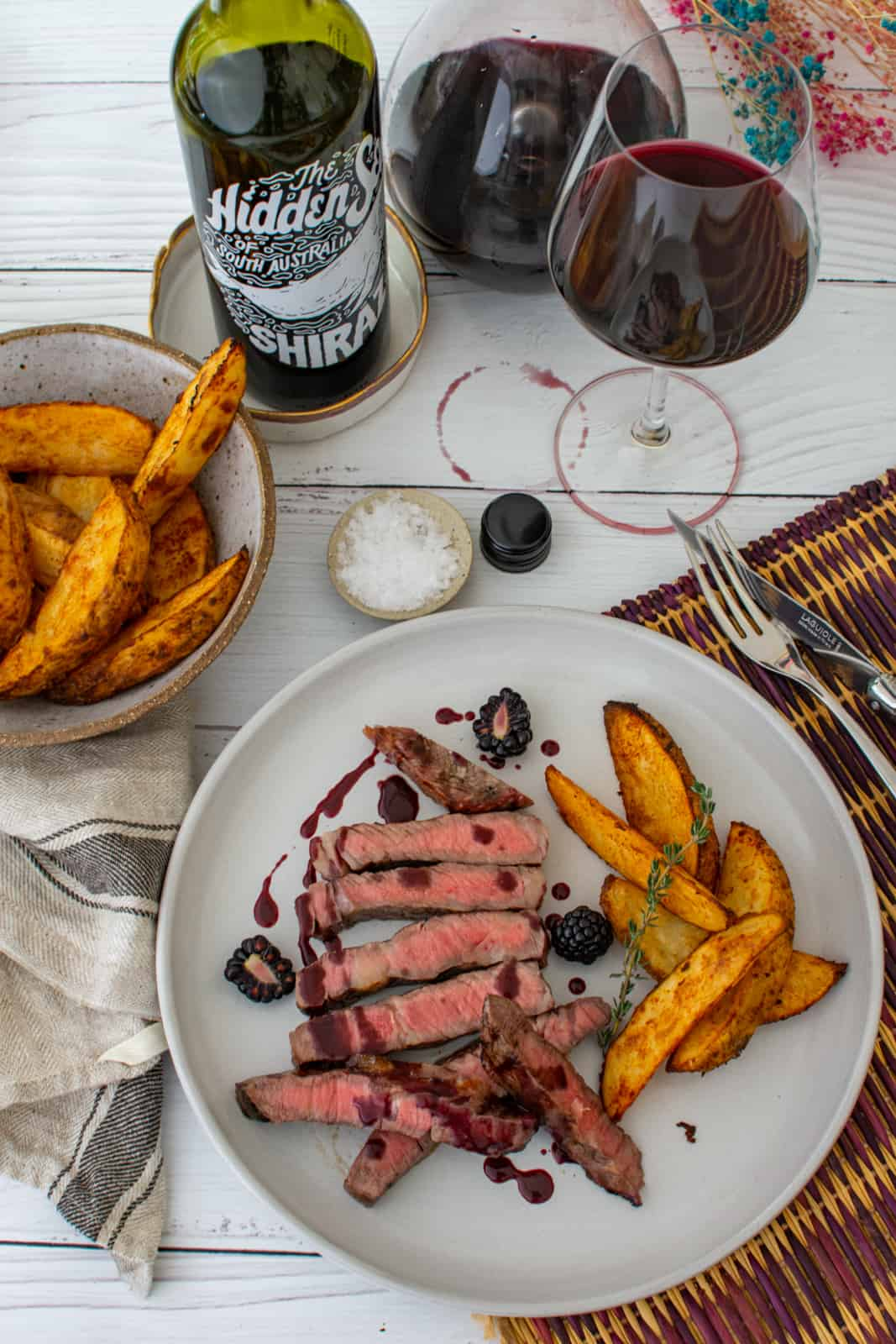 cooked scotch fillet, spicy potato wedges and blackberry jus on a plate with bowl of potato wedges and bottle of hidden sea shiraz next to it