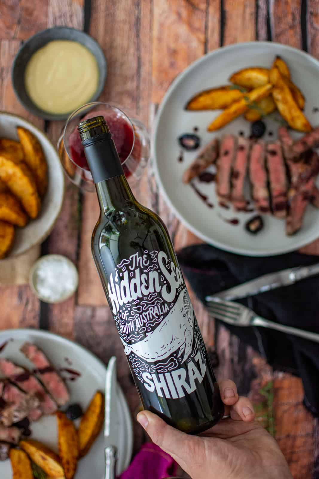close up of the hidden sea shiraz with food below on a wooden table