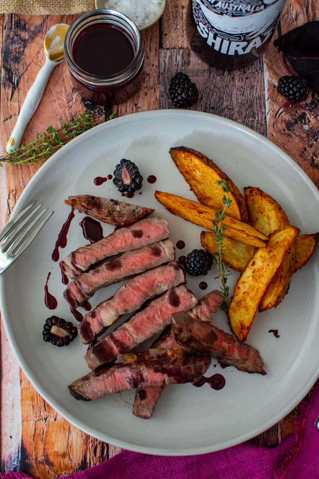 grilled scotch fillet on a plate with spicy wedges and blackberry jus
