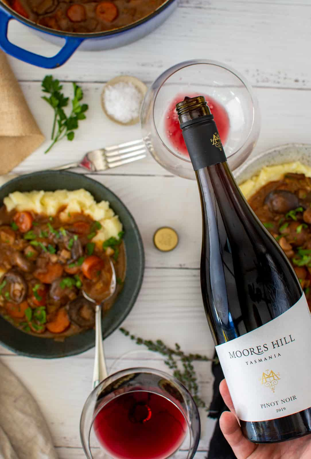 moores hill pinot noir being poured, bowls of stew on a white table beneath