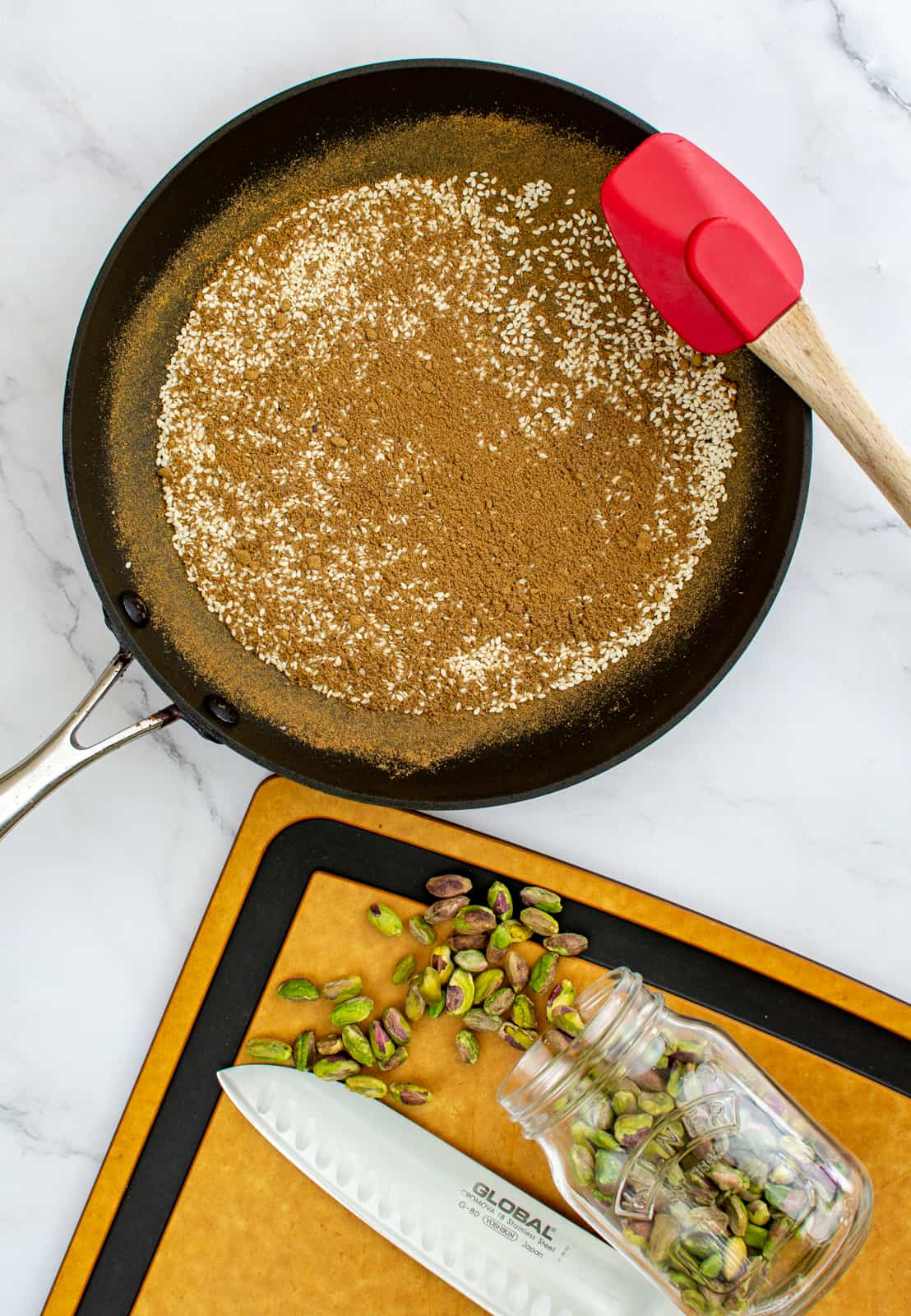 spices toasting in frying pan, pistachio on a chopping board
