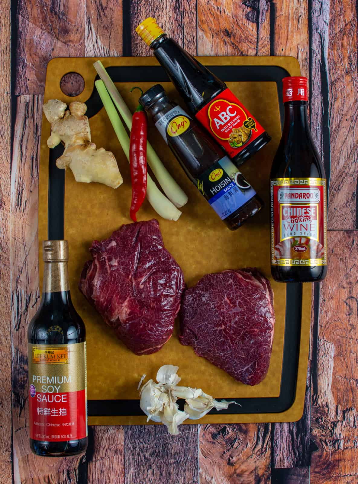 ingredients for slow cooked beef cheeks on a wooden chopping board