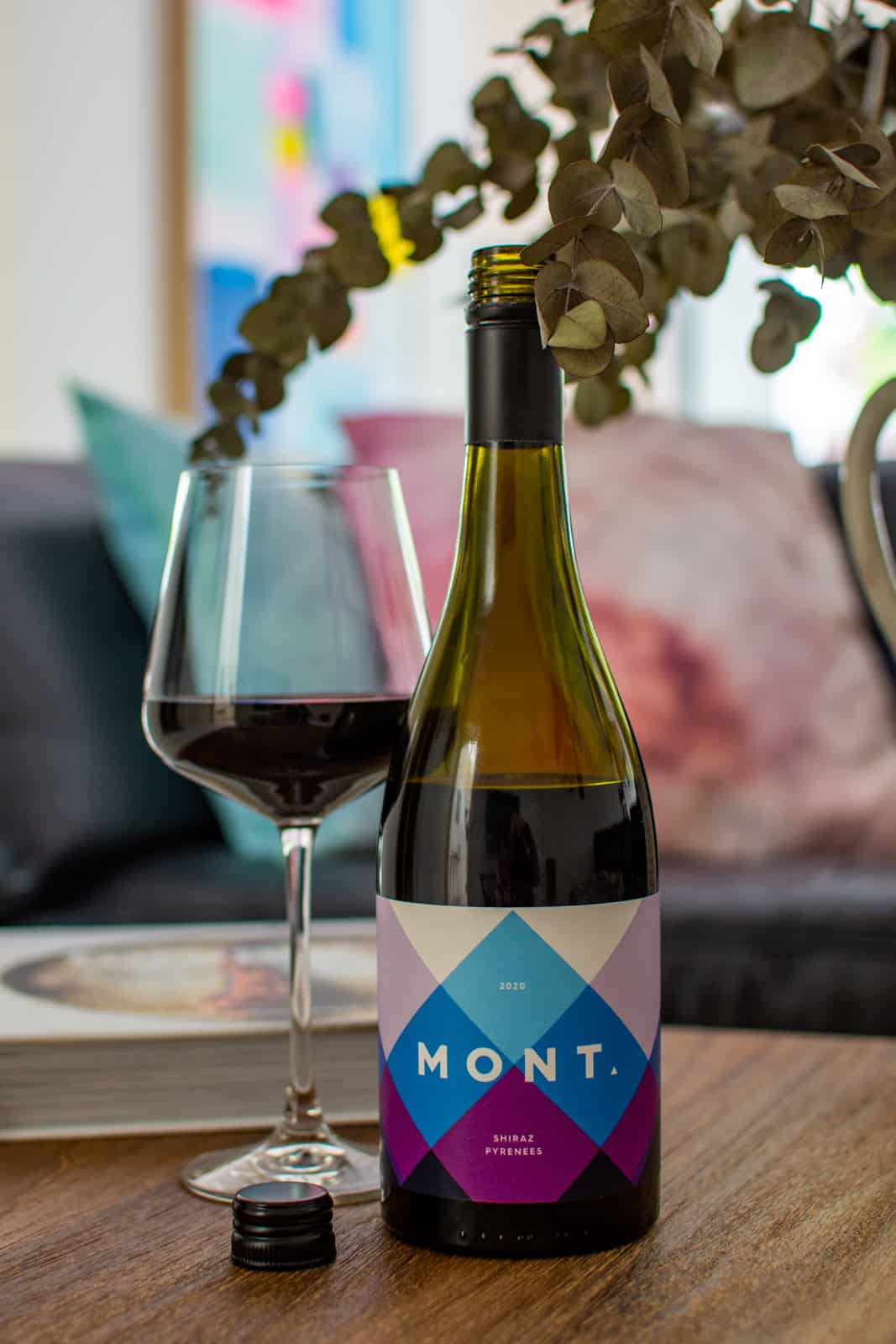 mont wines shiraz bottle and wine glass next to dried flowers