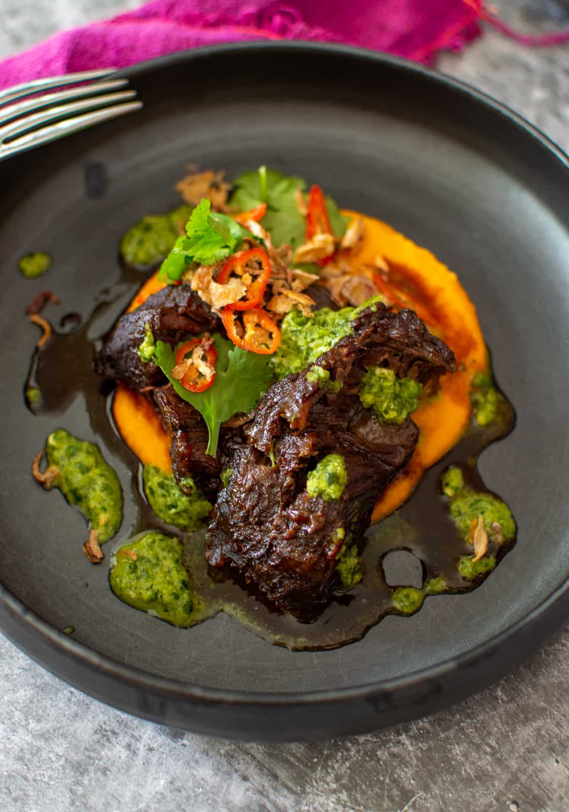 asian slow cooked beef cheeks in a black bowl with nam prik dressing