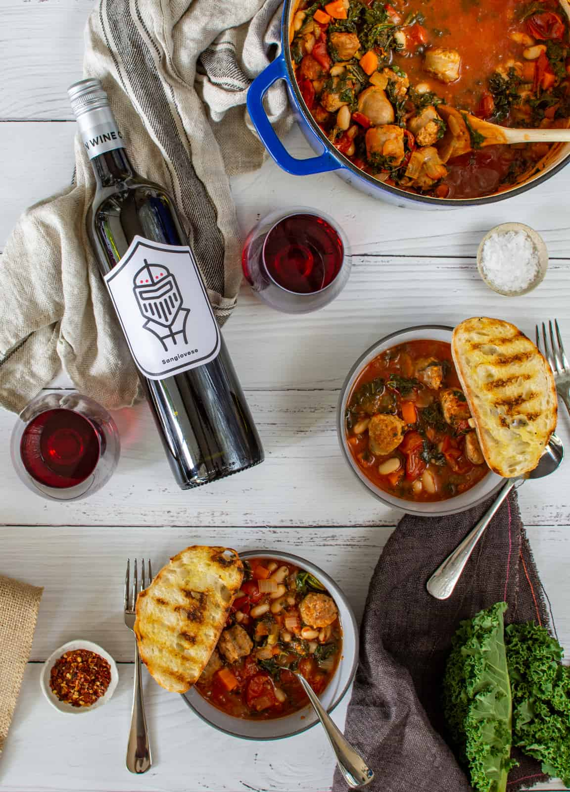 tuscan sausage stew in blue casserole dish, bowls of stew and pawn wine co red wine on a white table