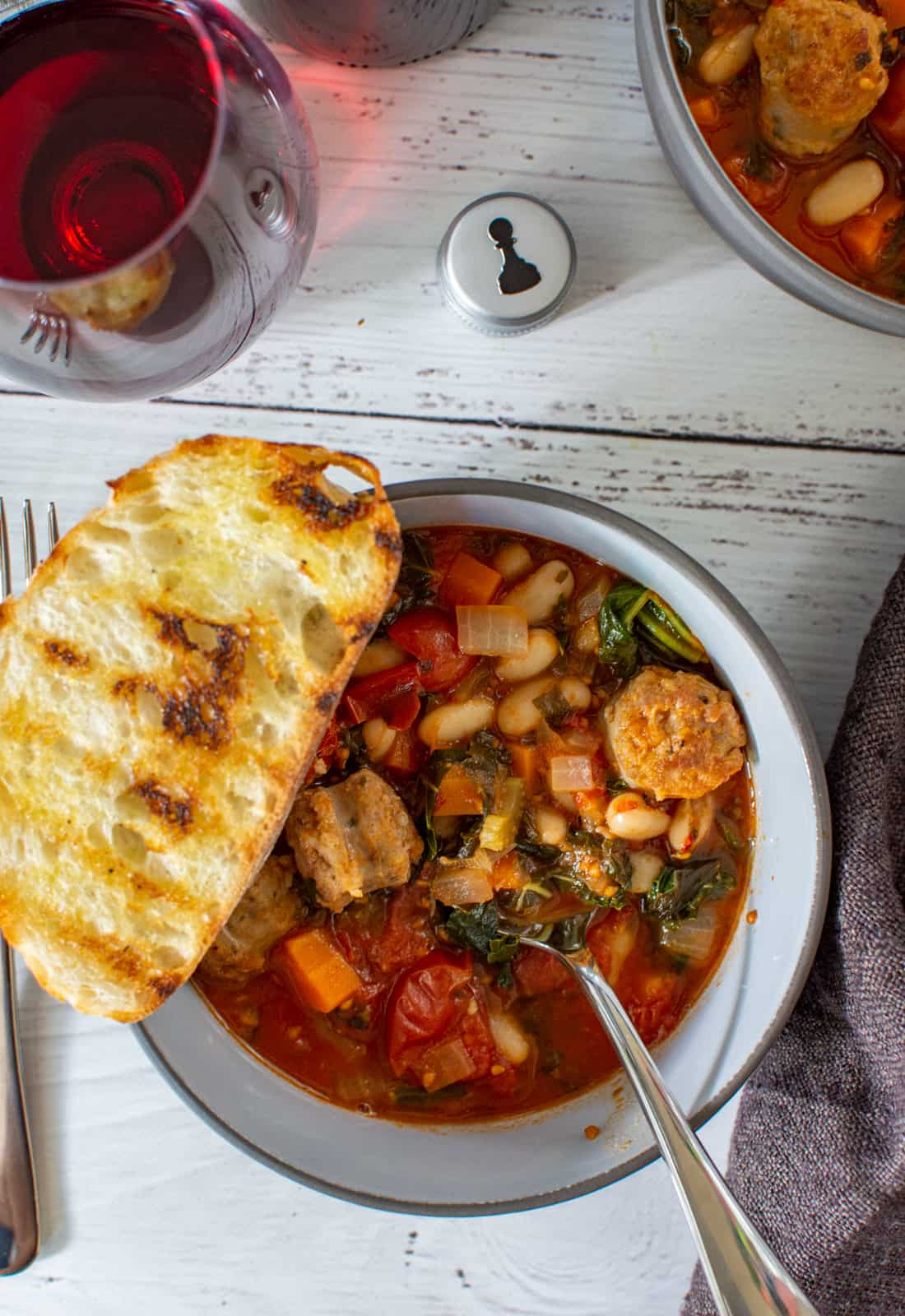 bowl of tuscan sausage stew, red wine and pawn wine co bottle cap