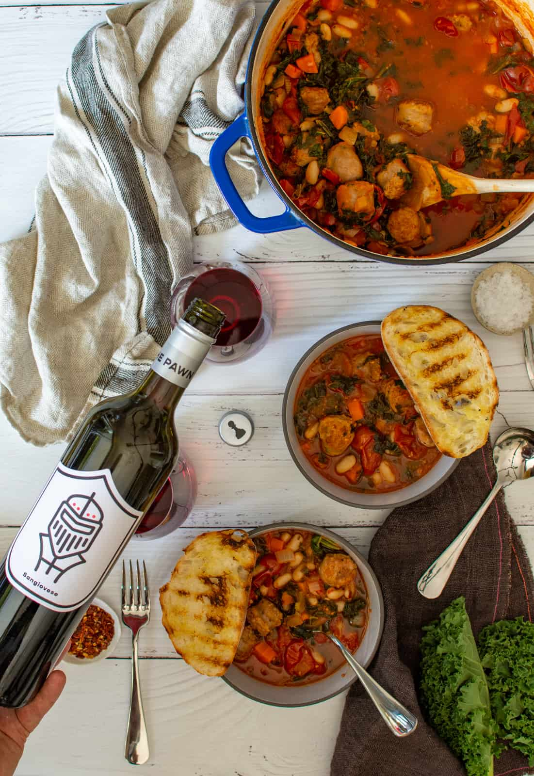 bowls of tuscan sausage stew on table with napkins and someone pouring pawn wine co sangiovese wine