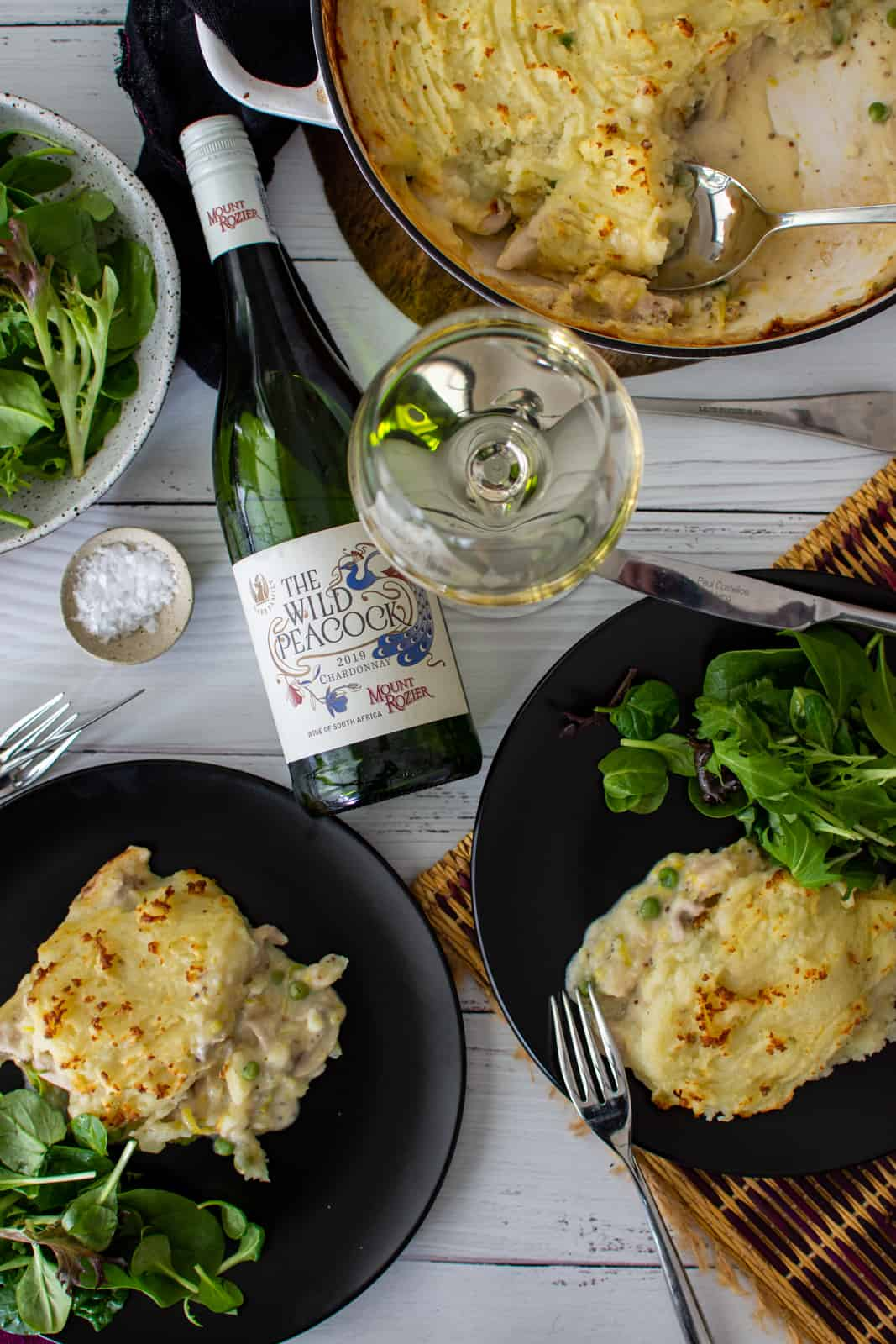 chicken and mushroom pie on plates with salad and a bottle of chardonnay next to them