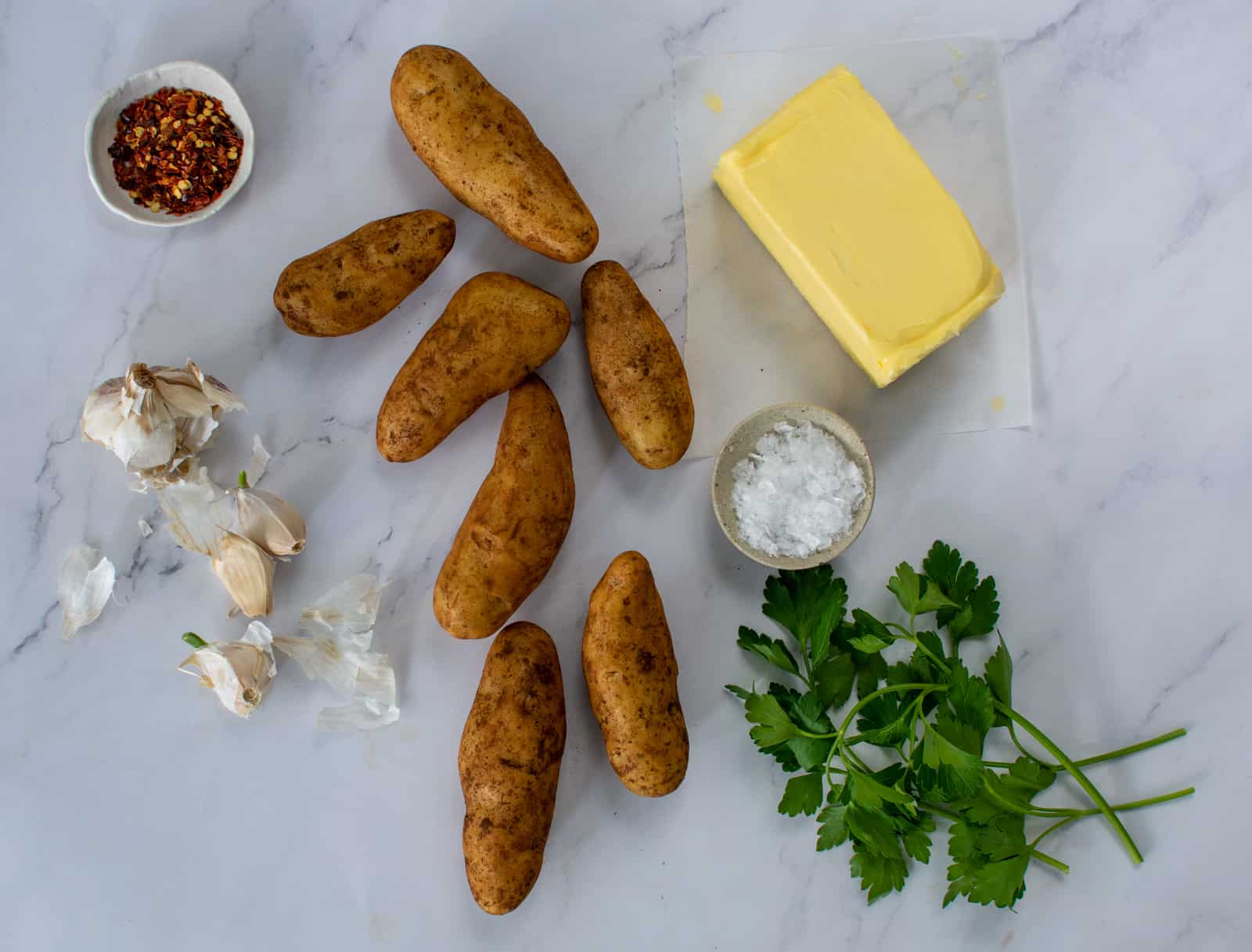 kipfler potatoes, butter, garlic and herbs on kitchen counter top