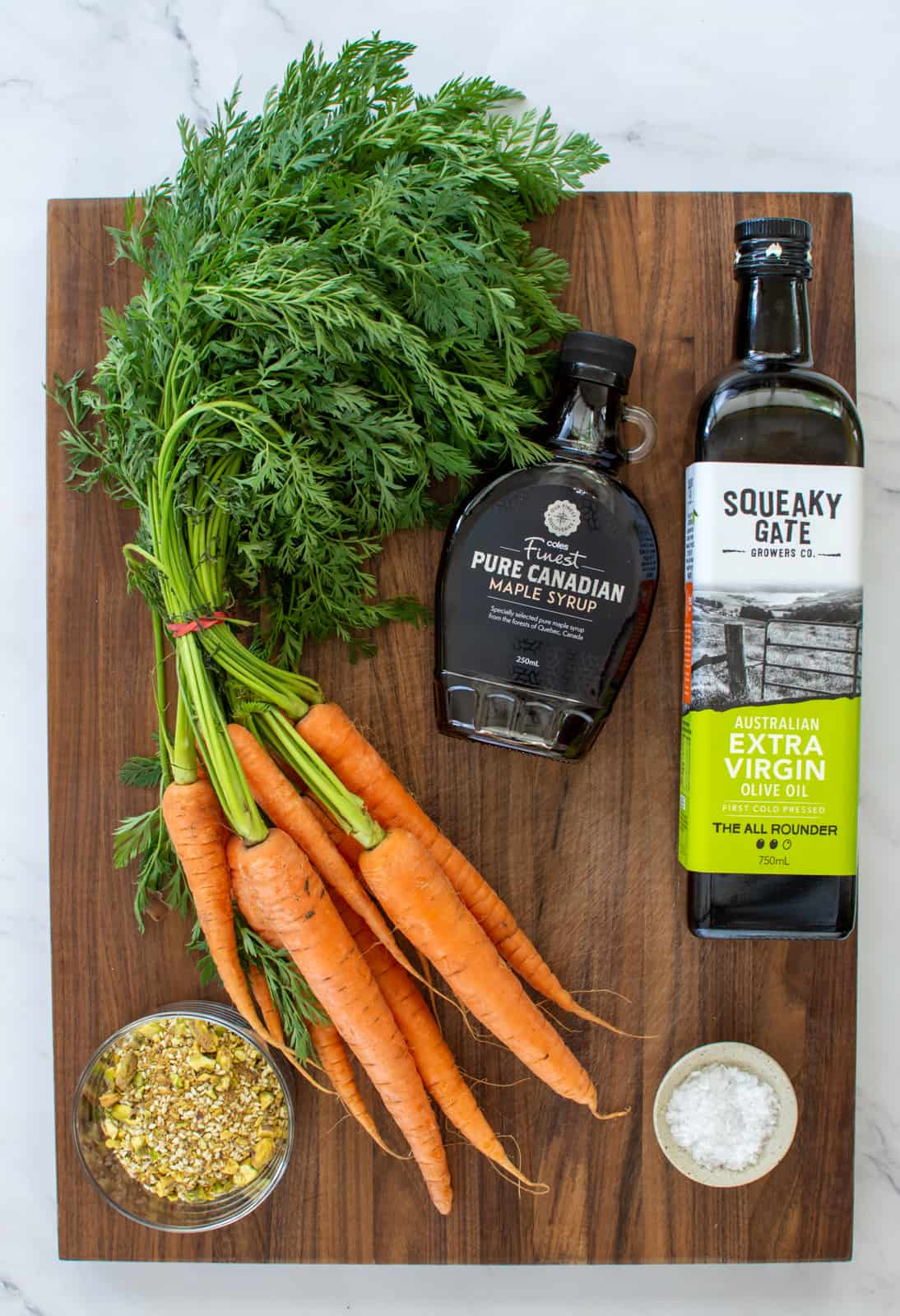 carrots, olive oil and maple syrup on a board