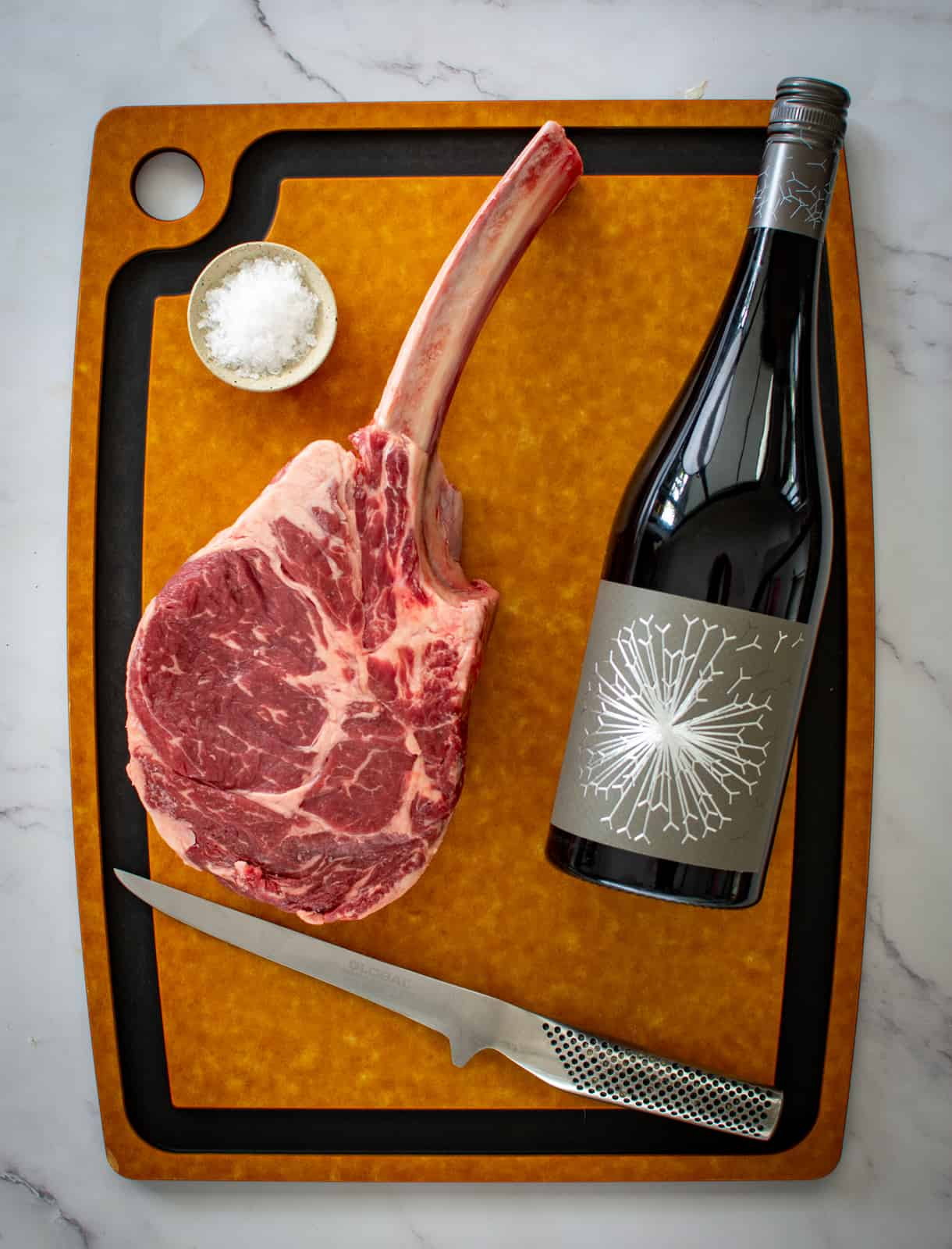 tomahawk steak and a bottle of wine on a chopping board