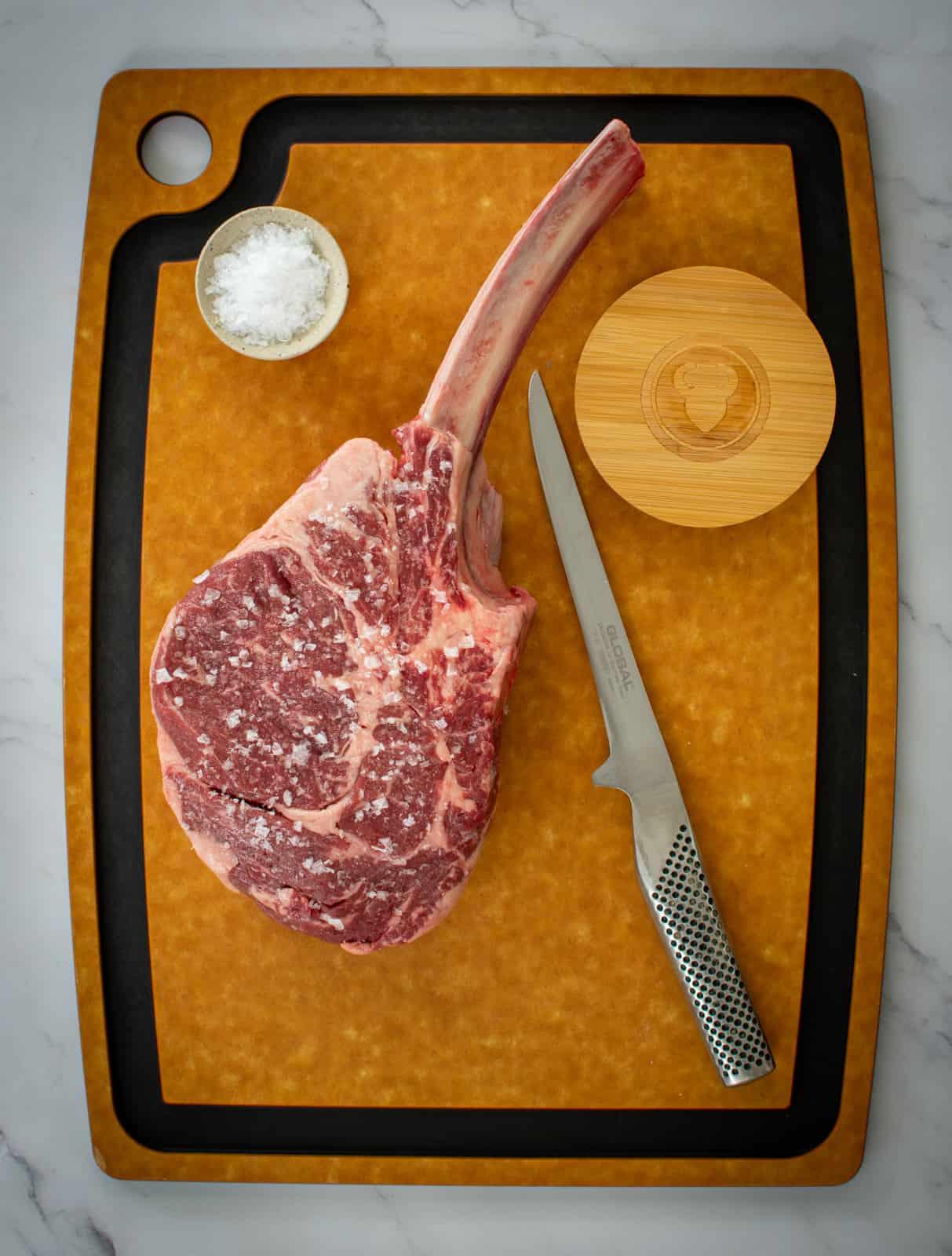tomahawk steak, global knife and salt on chopping board
