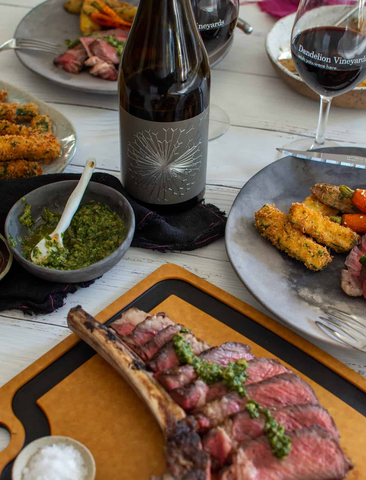 grilled tomahawk steak, wine and sides on a table